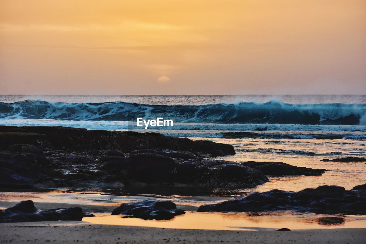 sea, water, sky, sunset, scenics - nature, beach, beauty in nature, horizon over water, land, wave, motion, horizon, nature, orange color, solid, rock, tranquility, tranquil scene, idyllic, no people, outdoors, power in nature
