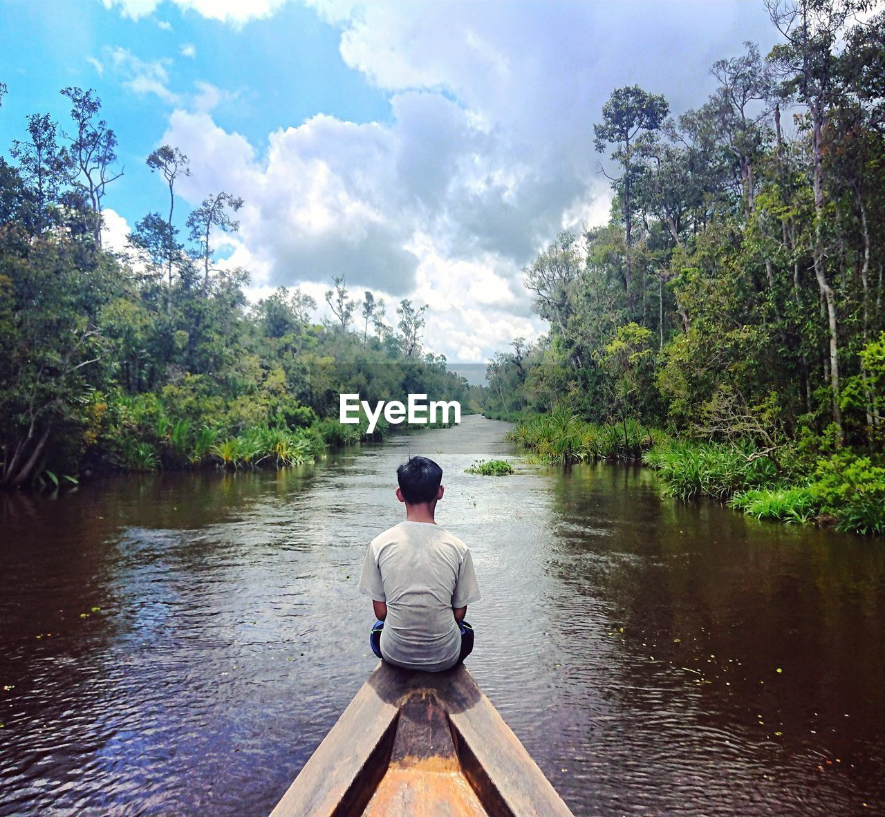 Rear view of man sitting in boat on river