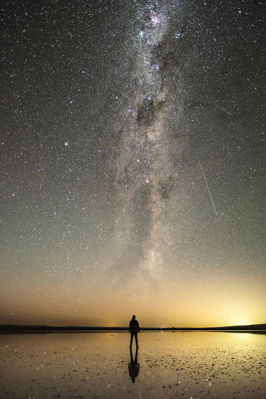 Silhouette Person Standing On Beach Against Sky At Night