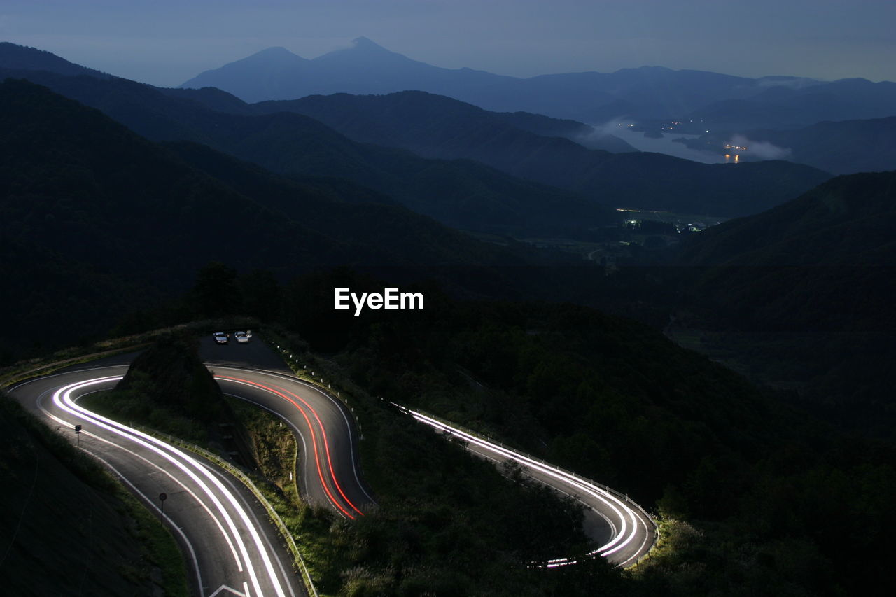 HIGH ANGLE VIEW OF LIGHT TRAILS ON MOUNTAIN ROAD AT NIGHT