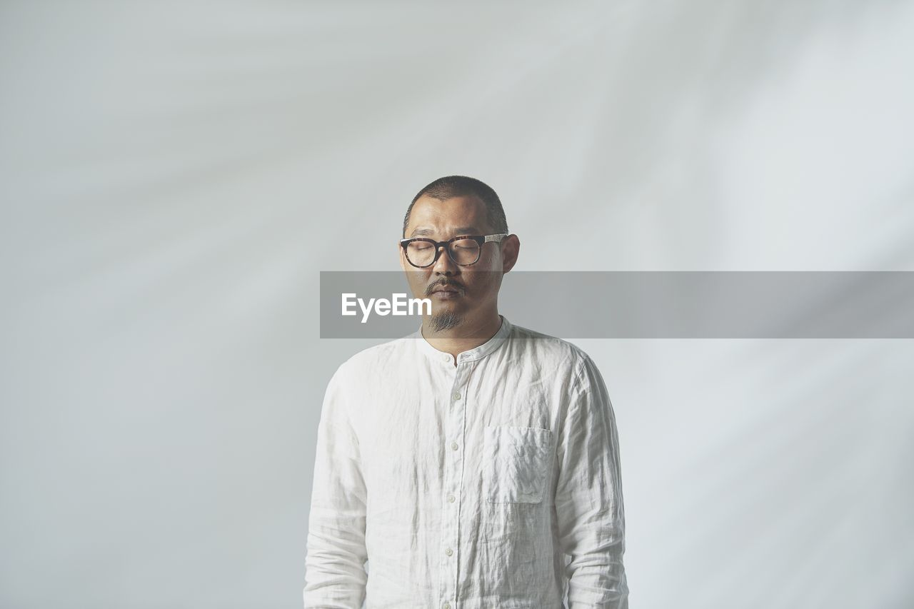 Man Standing With Eyes Closed Against White Background