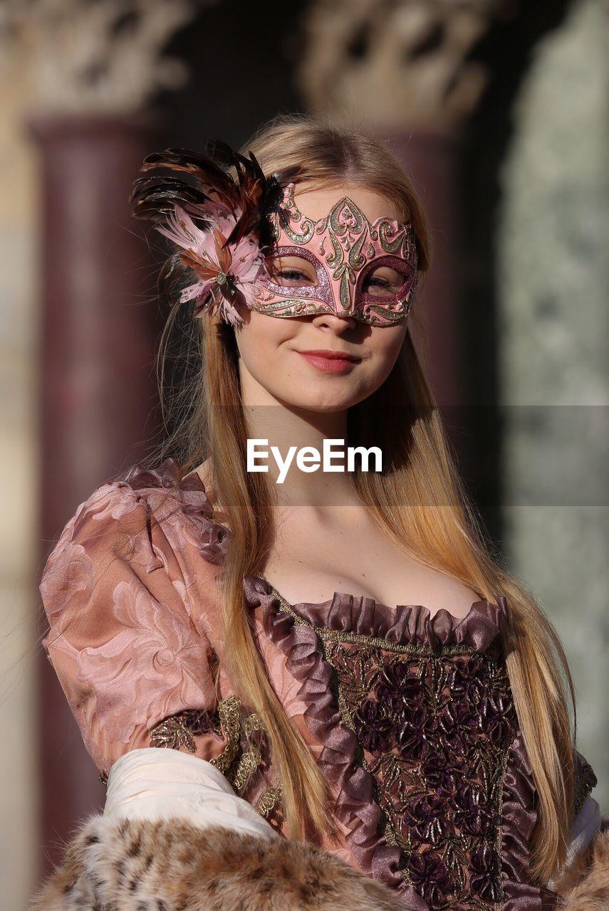 Portrait of smiling beautiful teenage girl wearing venetian mask