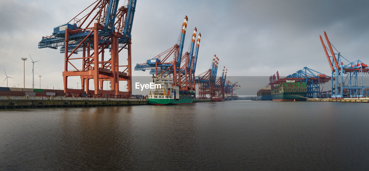 CRANES AT COMMERCIAL DOCK BY SEA AGAINST SKY
