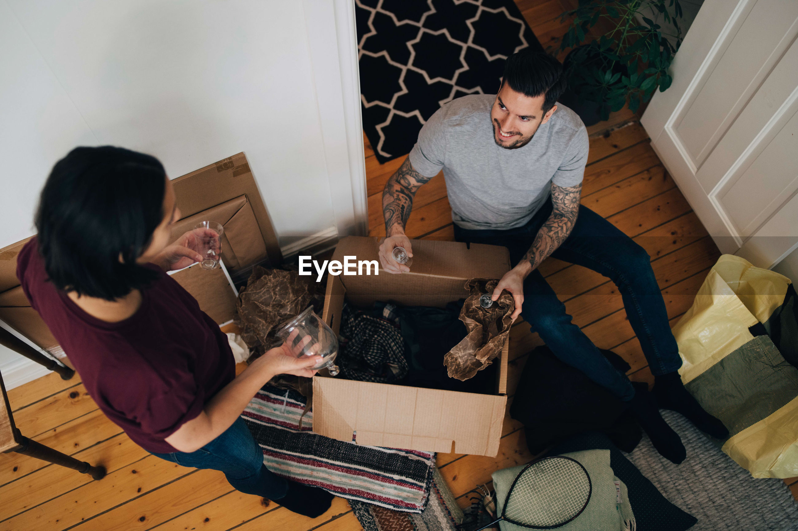 High angle view of man and woman unpacking box in living room