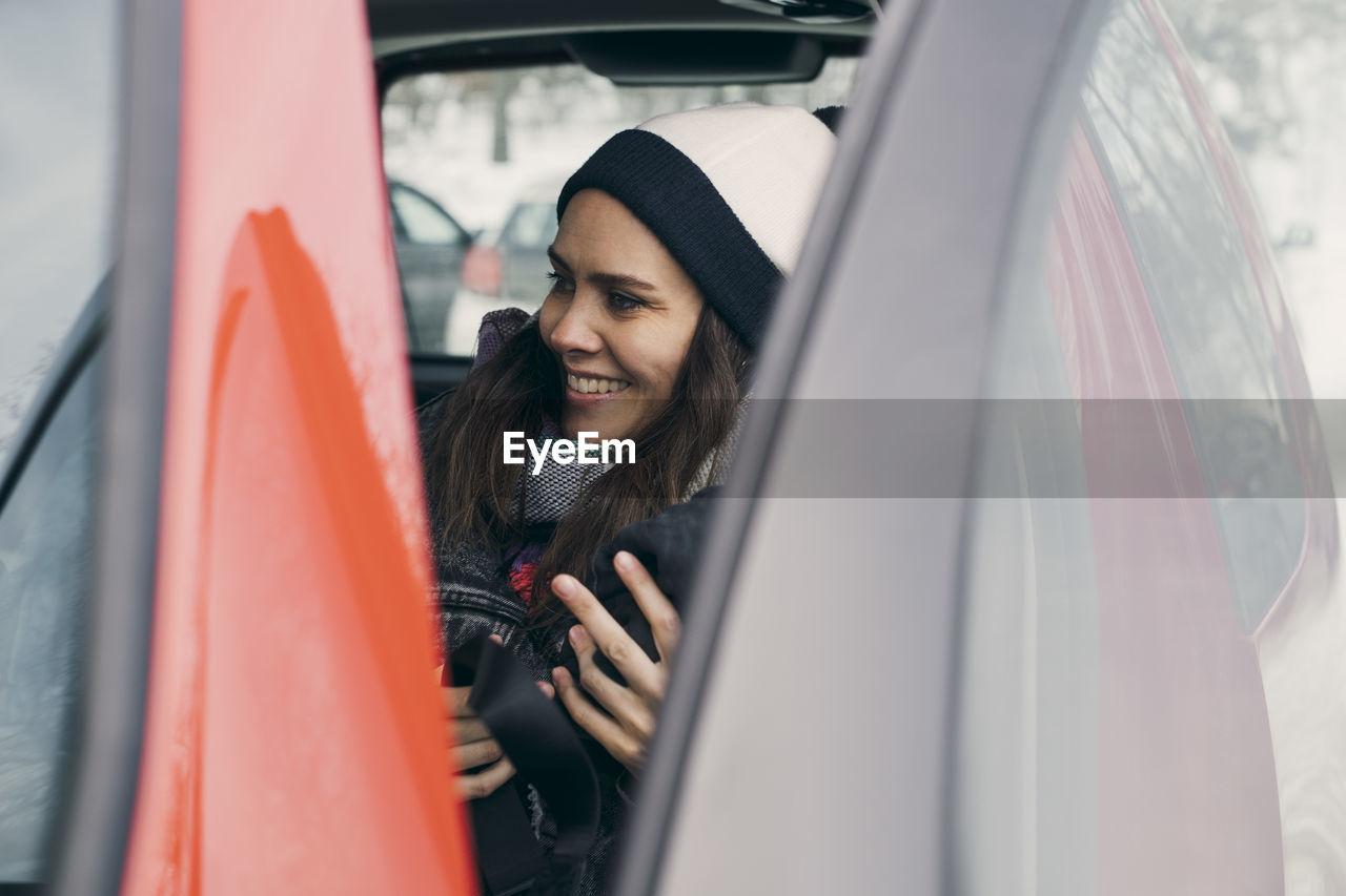 Smiling mid adult woman sitting in car seen through open door