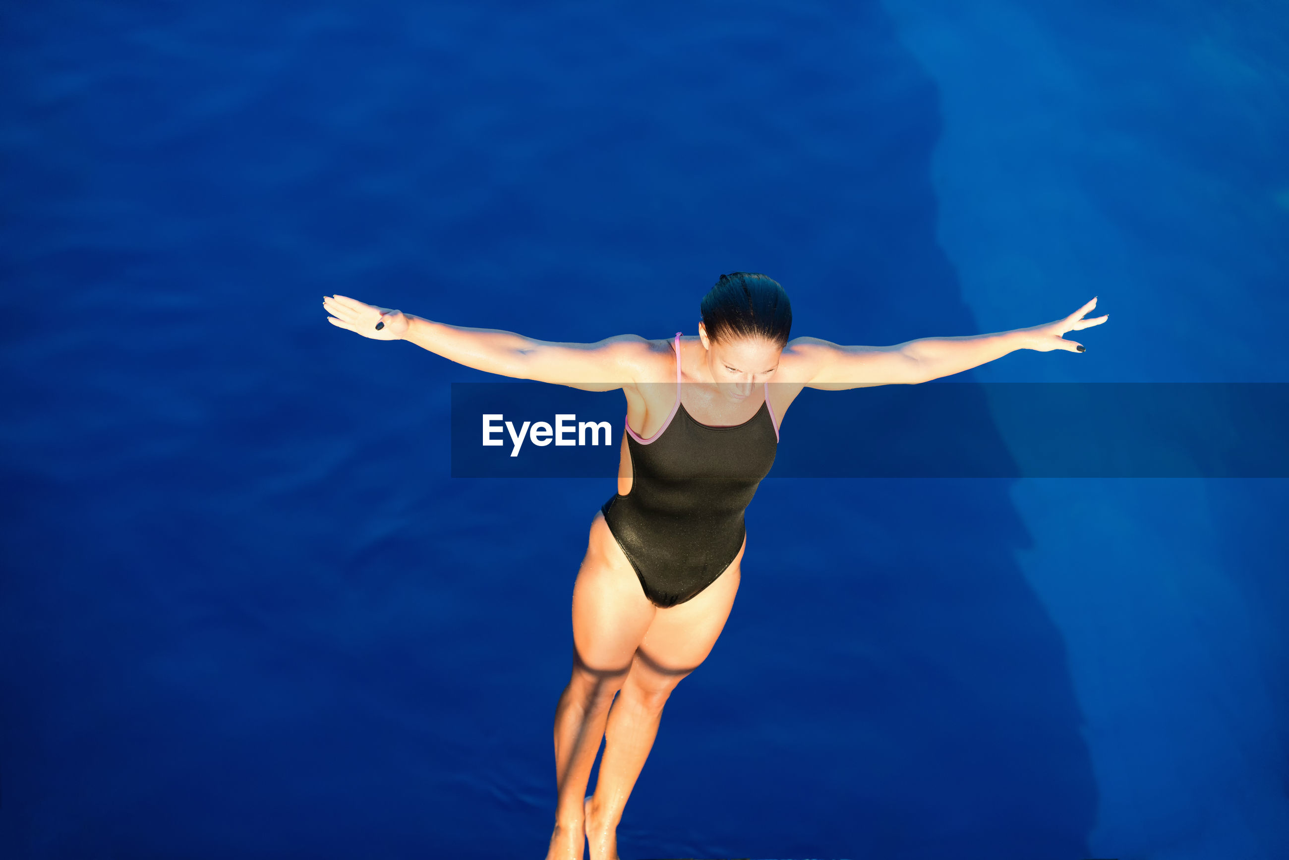 High angle view of woman with arms outstretched diving into swimming pool