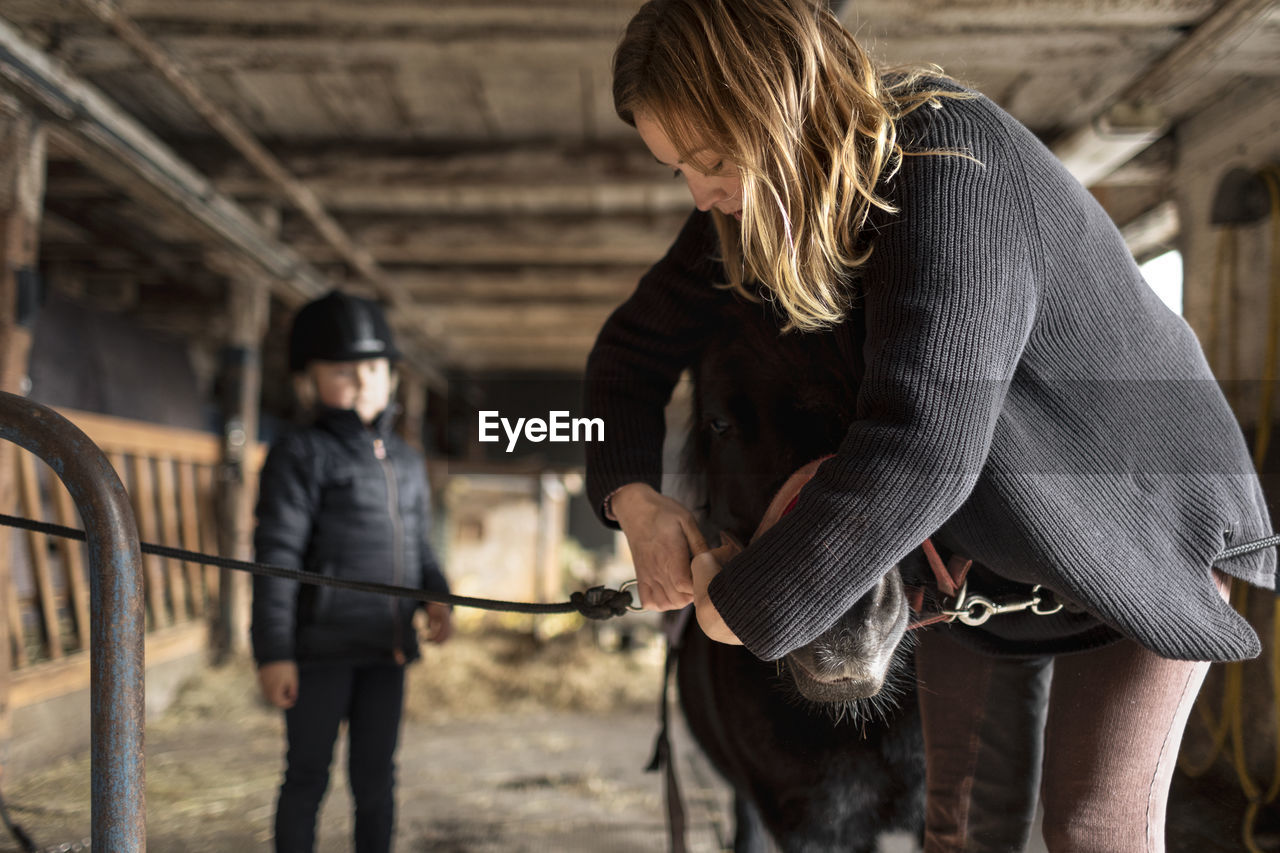 PEOPLE STANDING IN STABLE