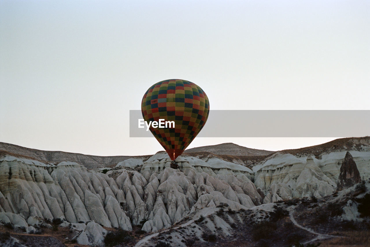 clear sky, hot air balloon, rock - object, copy space, nature, mountain, flying, day, outdoors, mid-air, no people, scenics, beauty in nature, adventure, landscape, ballooning festival, sky