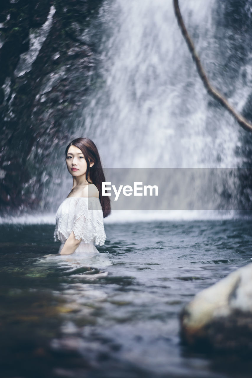 Beautiful woman in river against waterfall