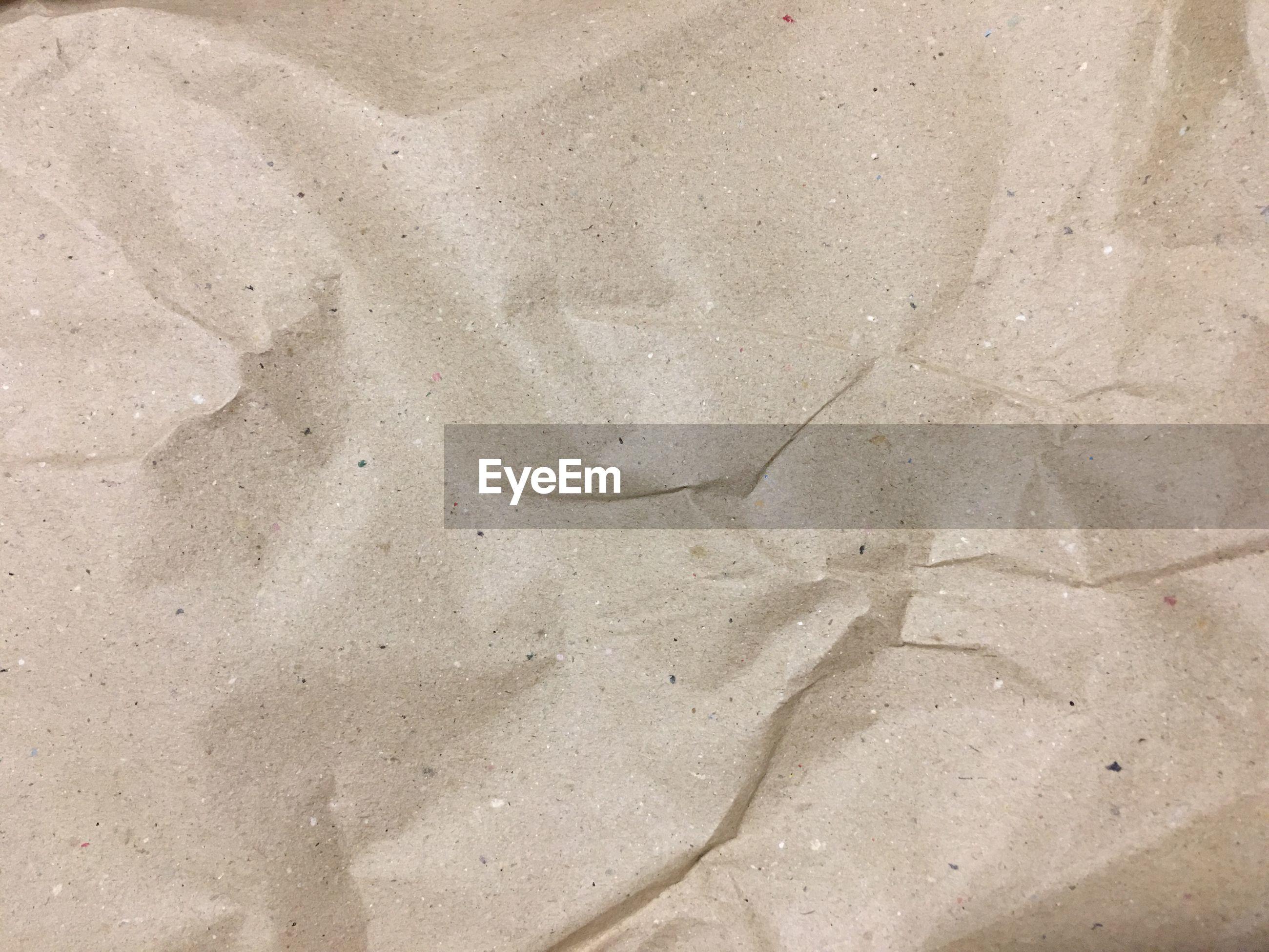 Full frame shot of beige crumpled paper