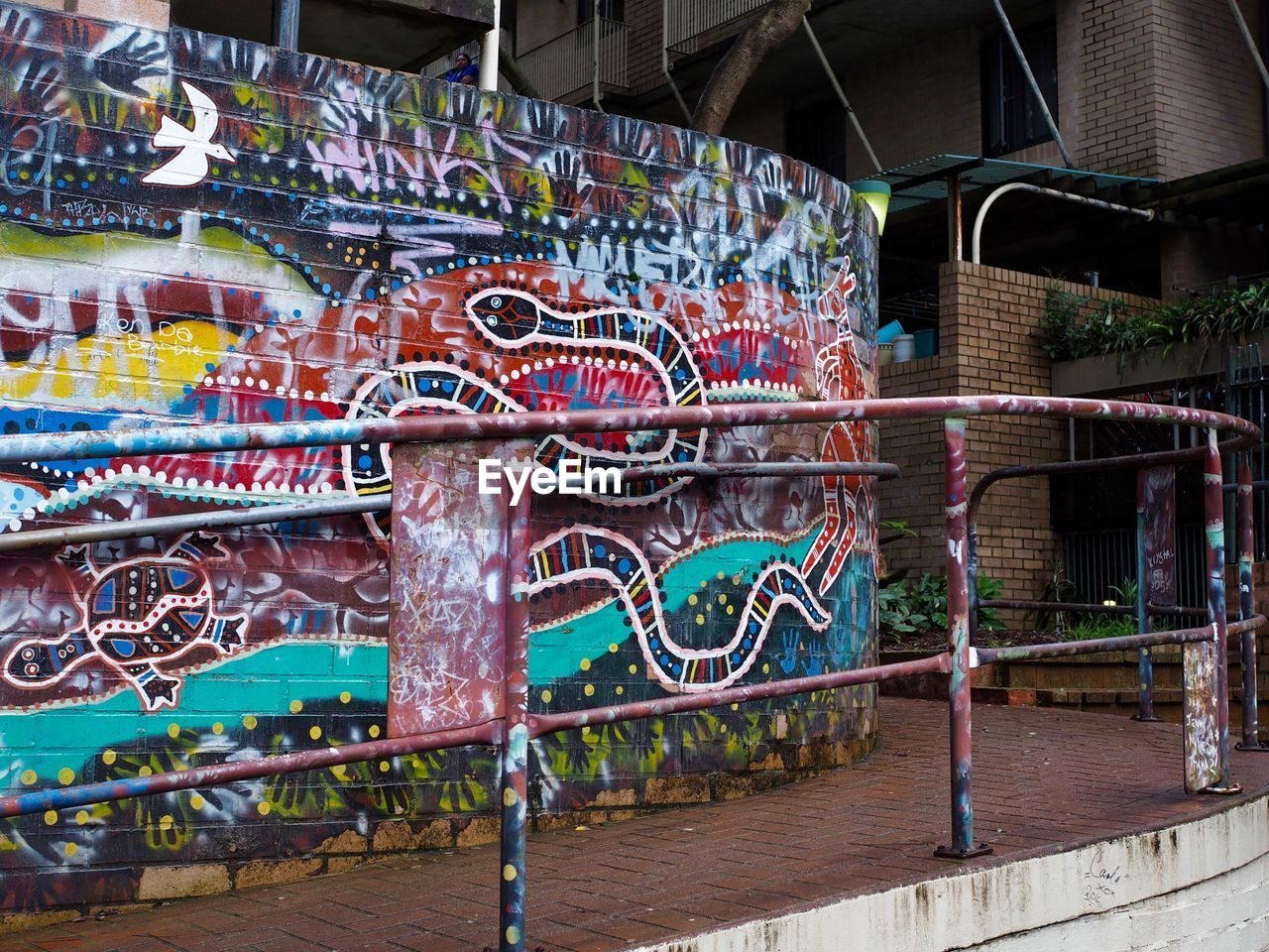 graffiti, street art, multi colored, amusement park, built structure, motion, no people, architecture, day, water, outdoors, building exterior, spraying, carousel, close-up