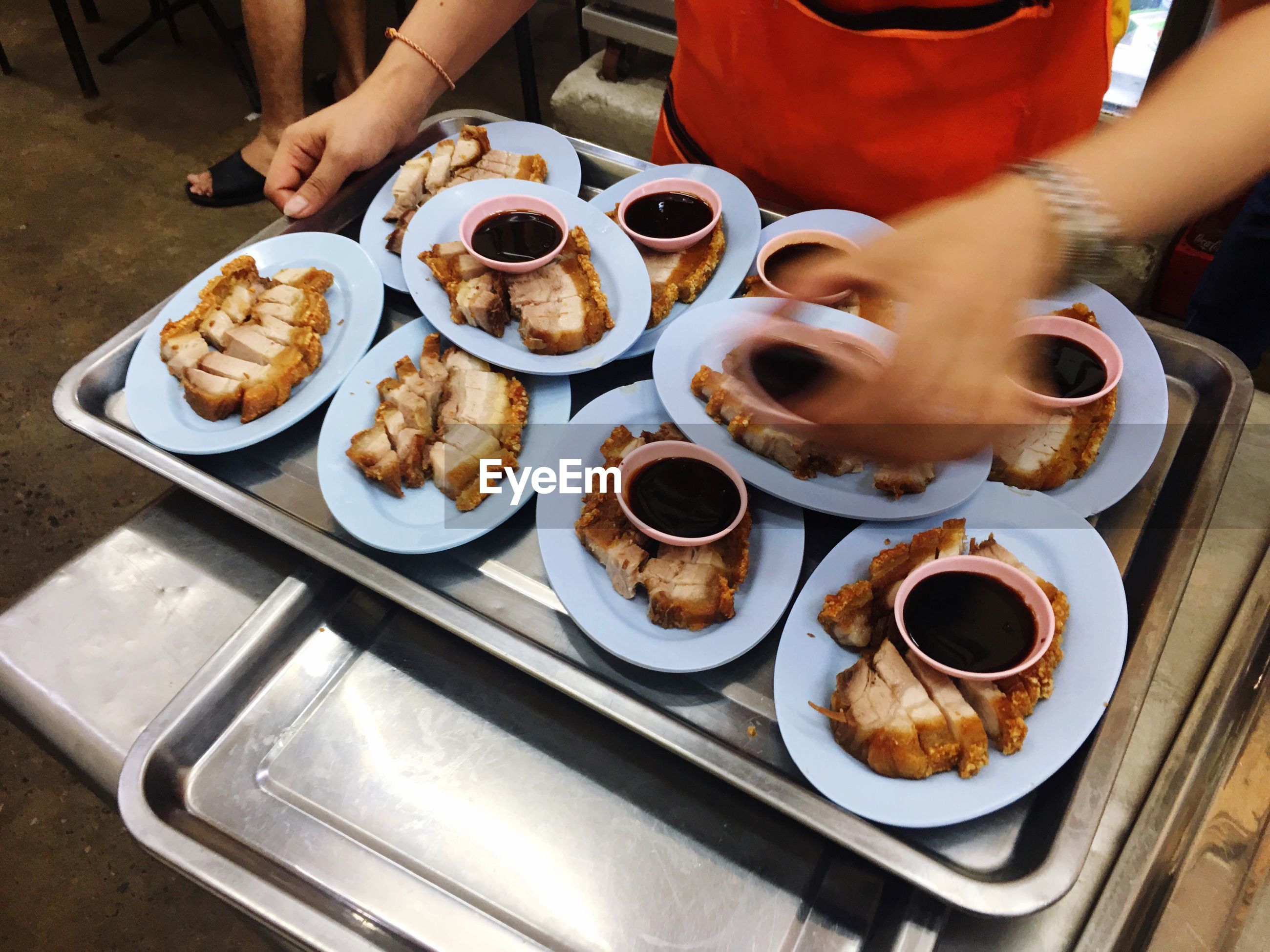 Midsection of waiter holding food plates in tray