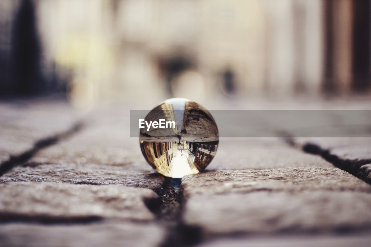 Buildings reflecting in crystal ball on footpath