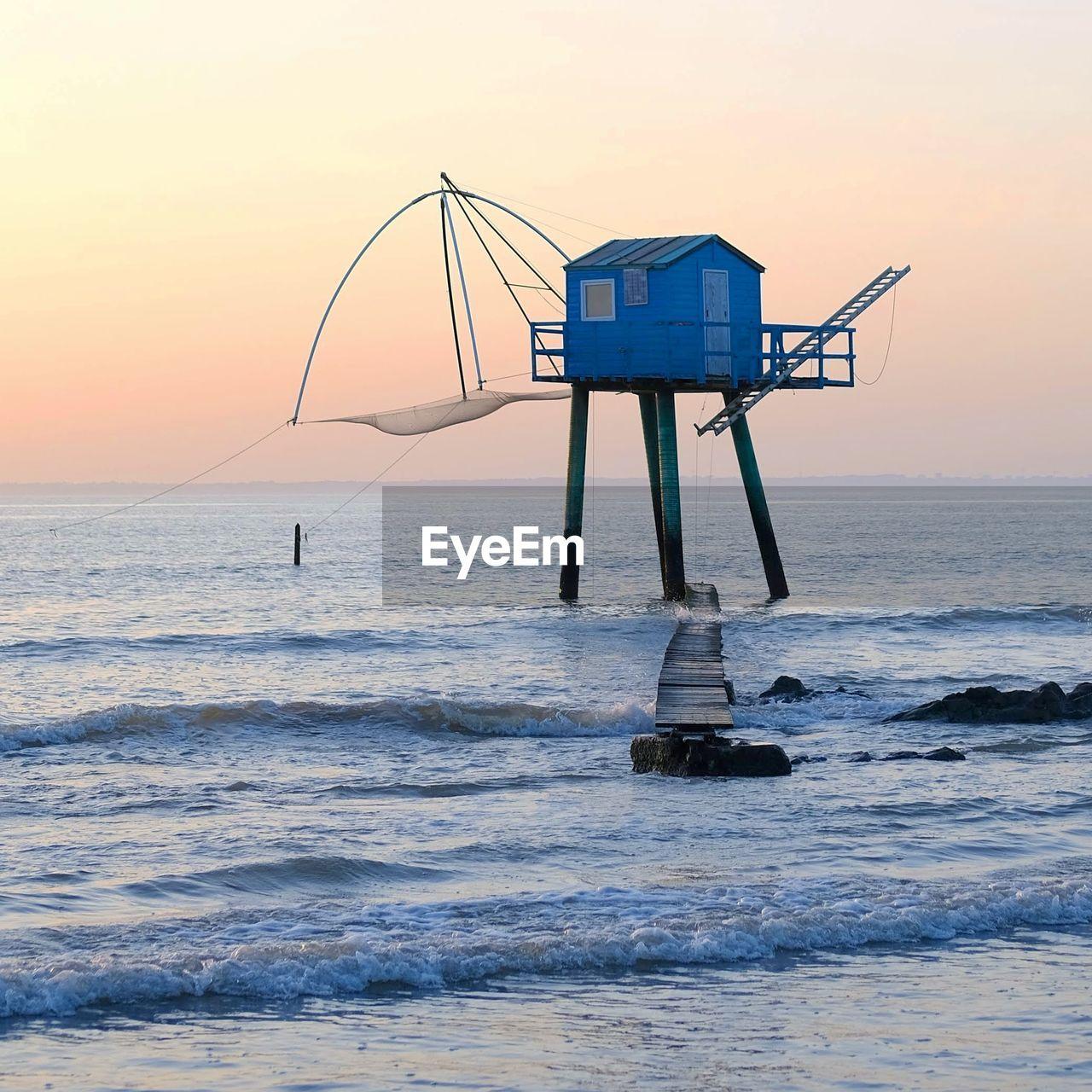 LIFEGUARD HUT ON SEA AGAINST SKY