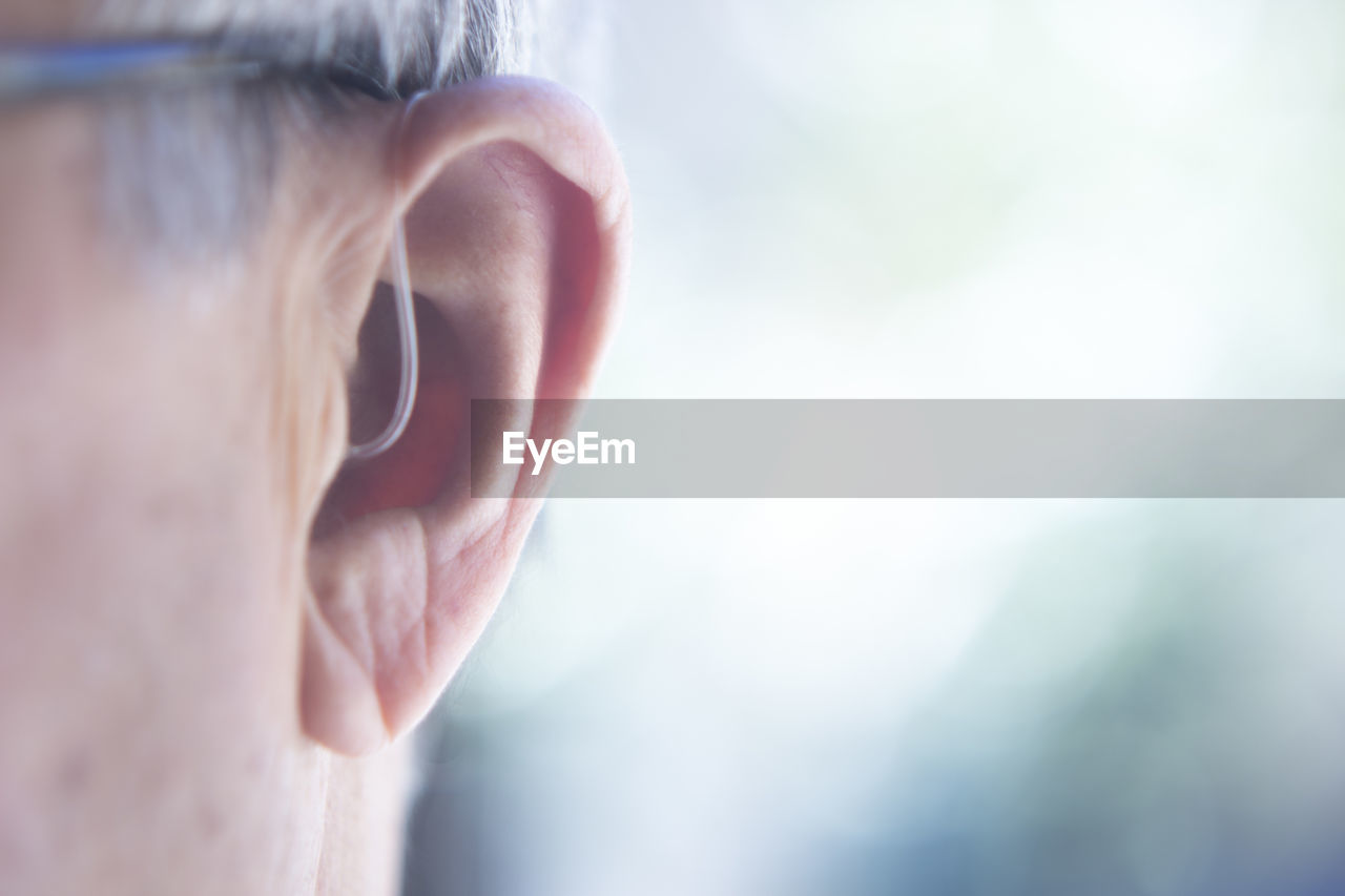 Close-Up Of Man With Hearing Aid Against Blurred Background