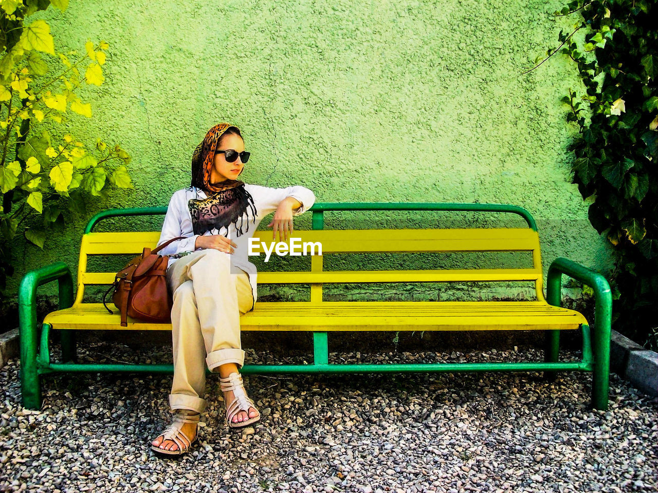 yellow, full length, sitting, young adult, one person, young women, long hair, casual clothing, real people, front view, relaxation, leisure activity, legs crossed at knee, waiting, beautiful woman, day, leaf, outdoors, lifestyles, one young woman only, flower, adult, adults only, people