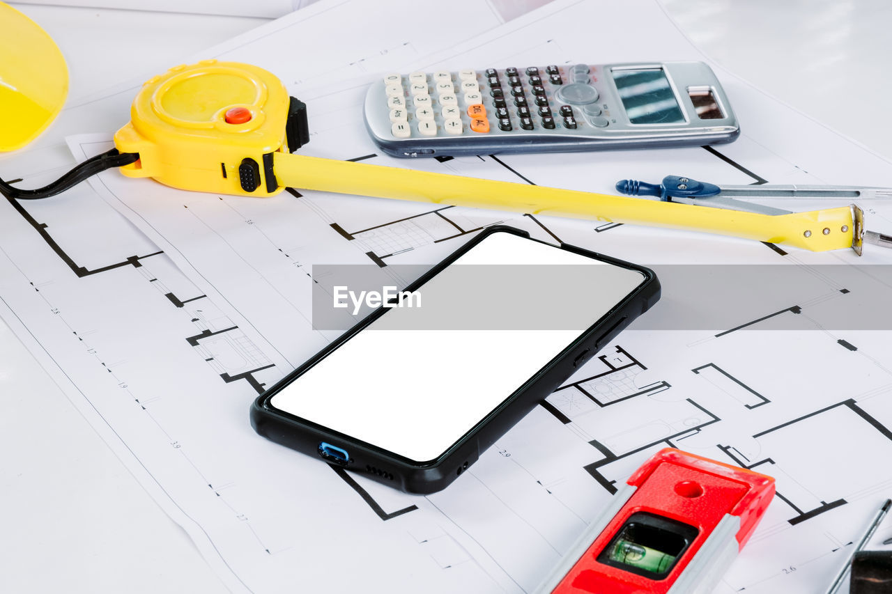technology, connection, wireless technology, portable information device, no people, communication, construction industry, blueprint, still life, mobile phone, indoors, high angle view, plan, smart phone, equipment, planning, industry, computer, close-up