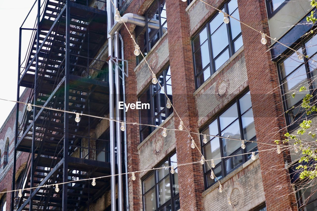 architecture, building exterior, built structure, low angle view, building, window, city, no people, day, industry, outdoors, glass - material, fire escape, brick, residential district, reflection, construction industry, full frame, text, nature, apartment