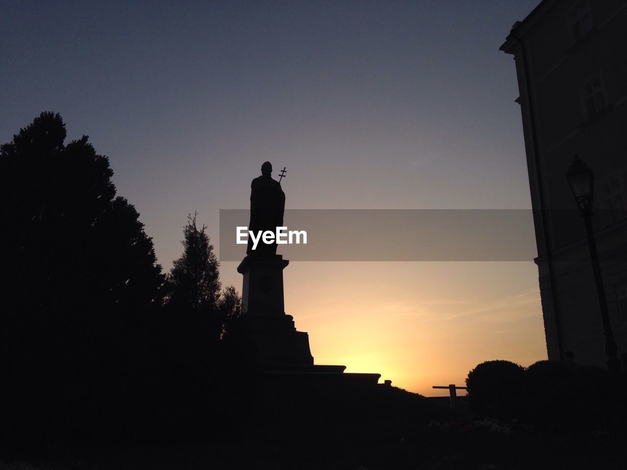 statue, sunset, human representation, silhouette, sculpture, male likeness, sky, outdoors, low angle view, architecture, built structure, no people, tree, nature, day