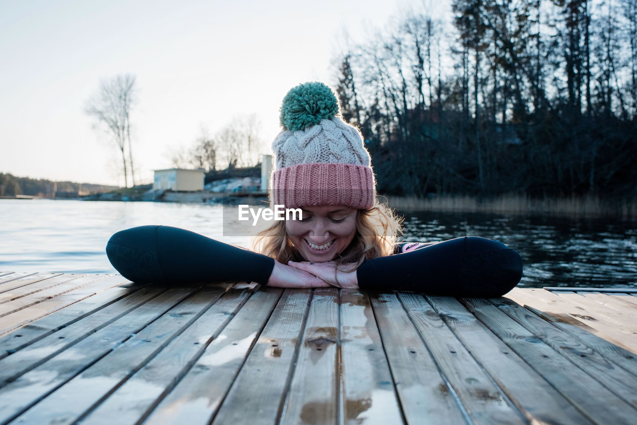 WOMAN SITTING ON WOOD BY LAKE AGAINST TREES DURING WINTER