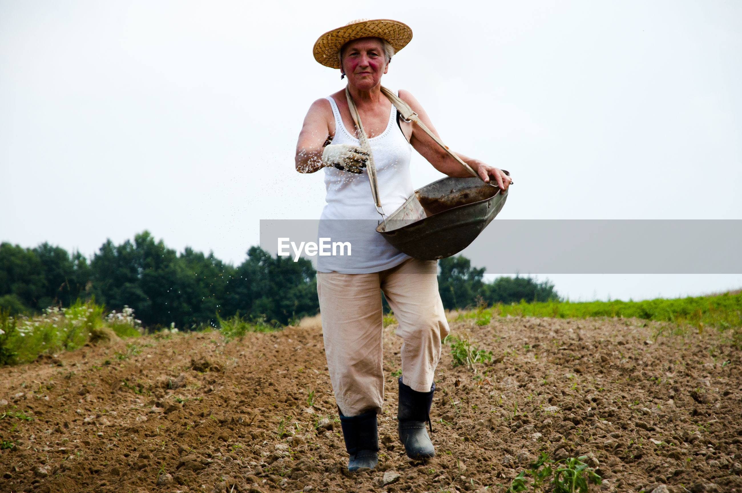 Full length portrait of female farmer walking on agricultural field