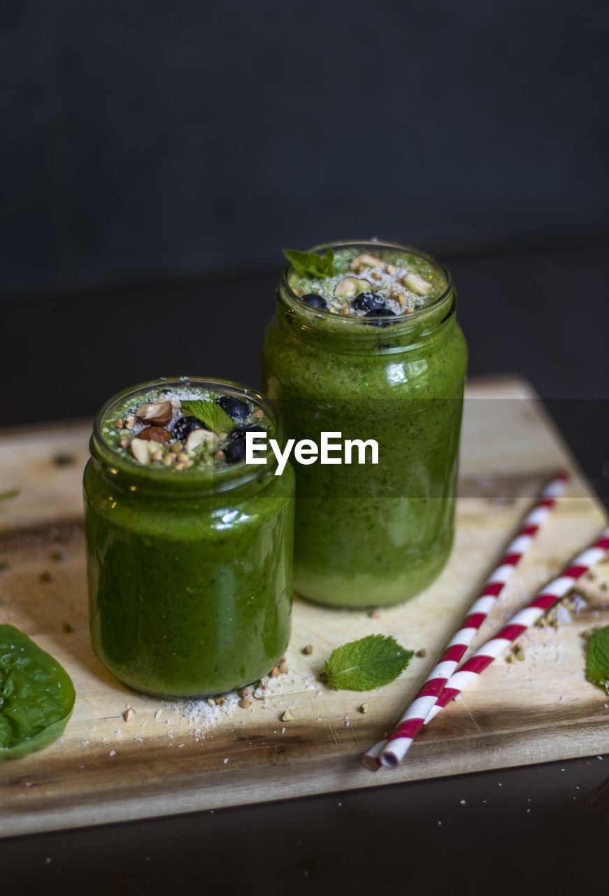 Close-up of green drink in jars on wood against black background