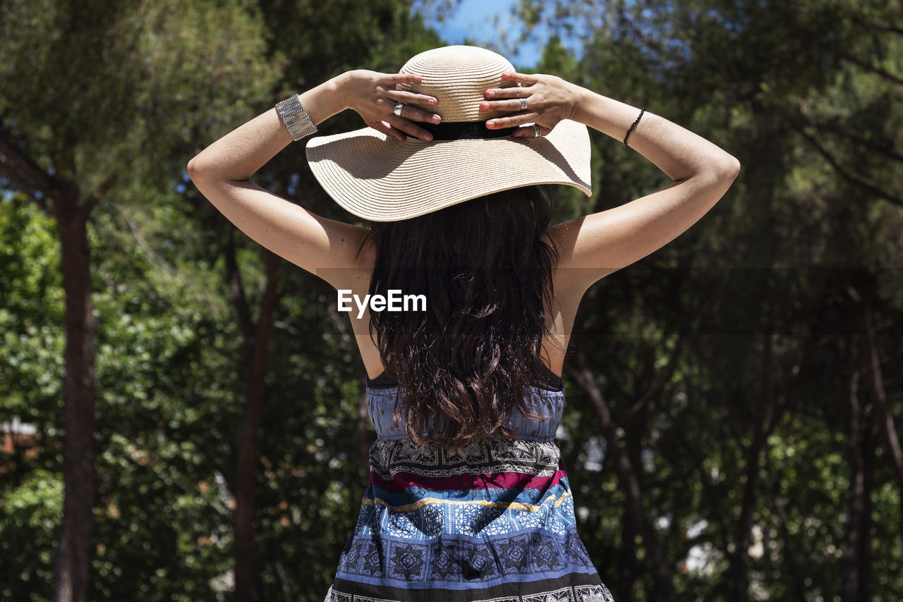 Rear View Of Woman Wearing Hat Standing Against Trees