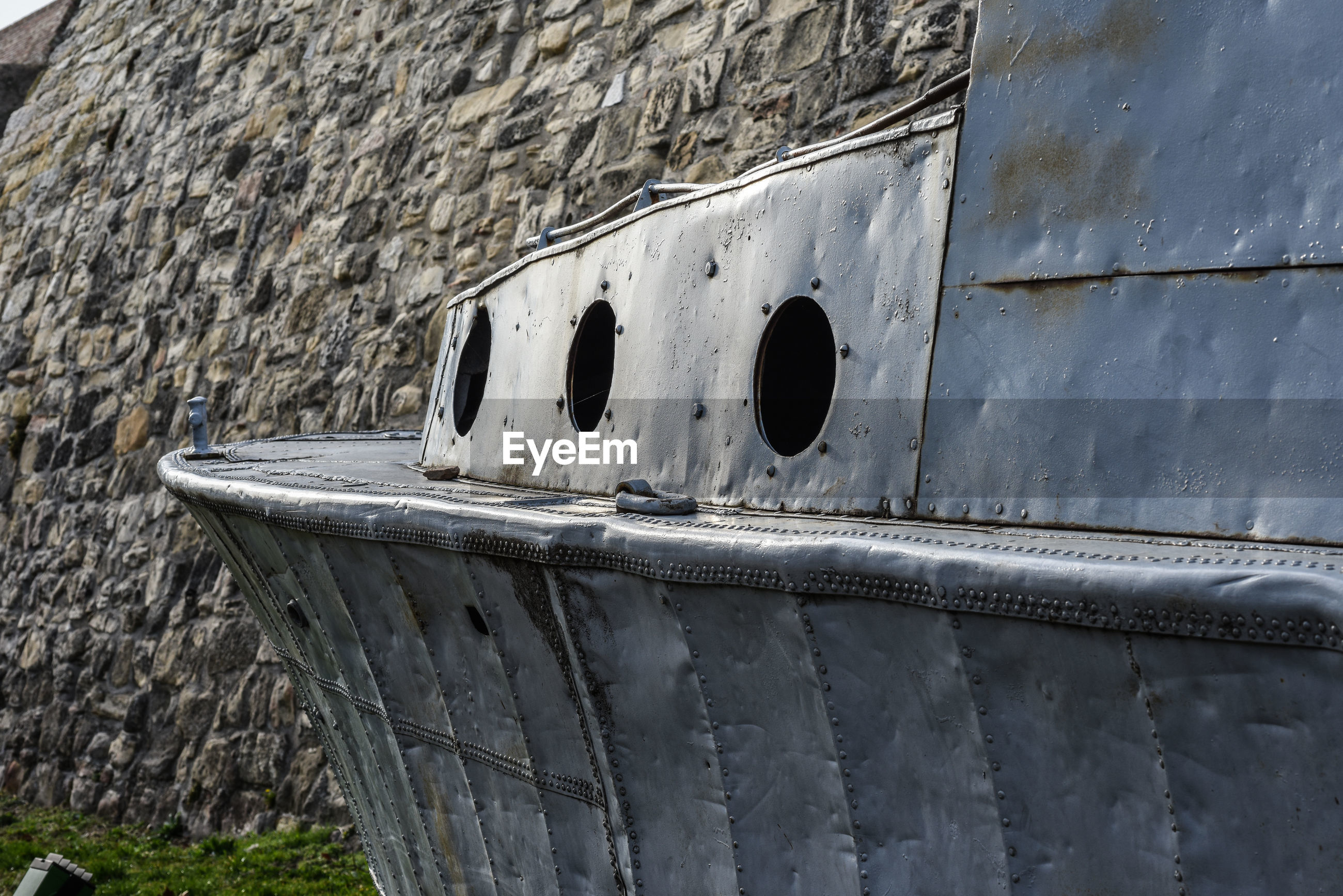 Low angle view of old boat against stone wall