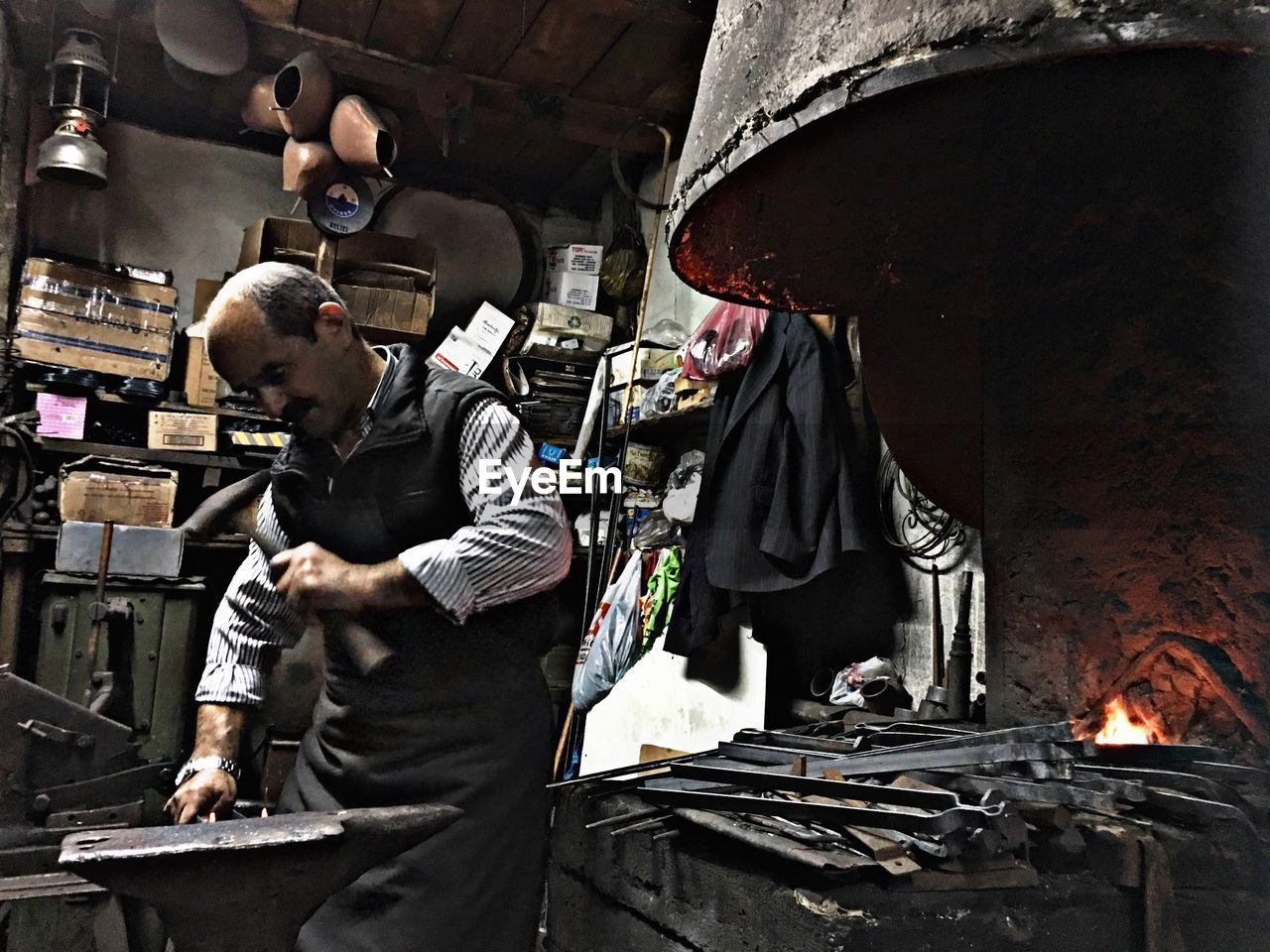 men, burning, real people, indoors, standing, occupation, working, people, fire, three quarter length, flame, fire - natural phenomenon, apron, business, heat - temperature, adult, holding, workshop, skill