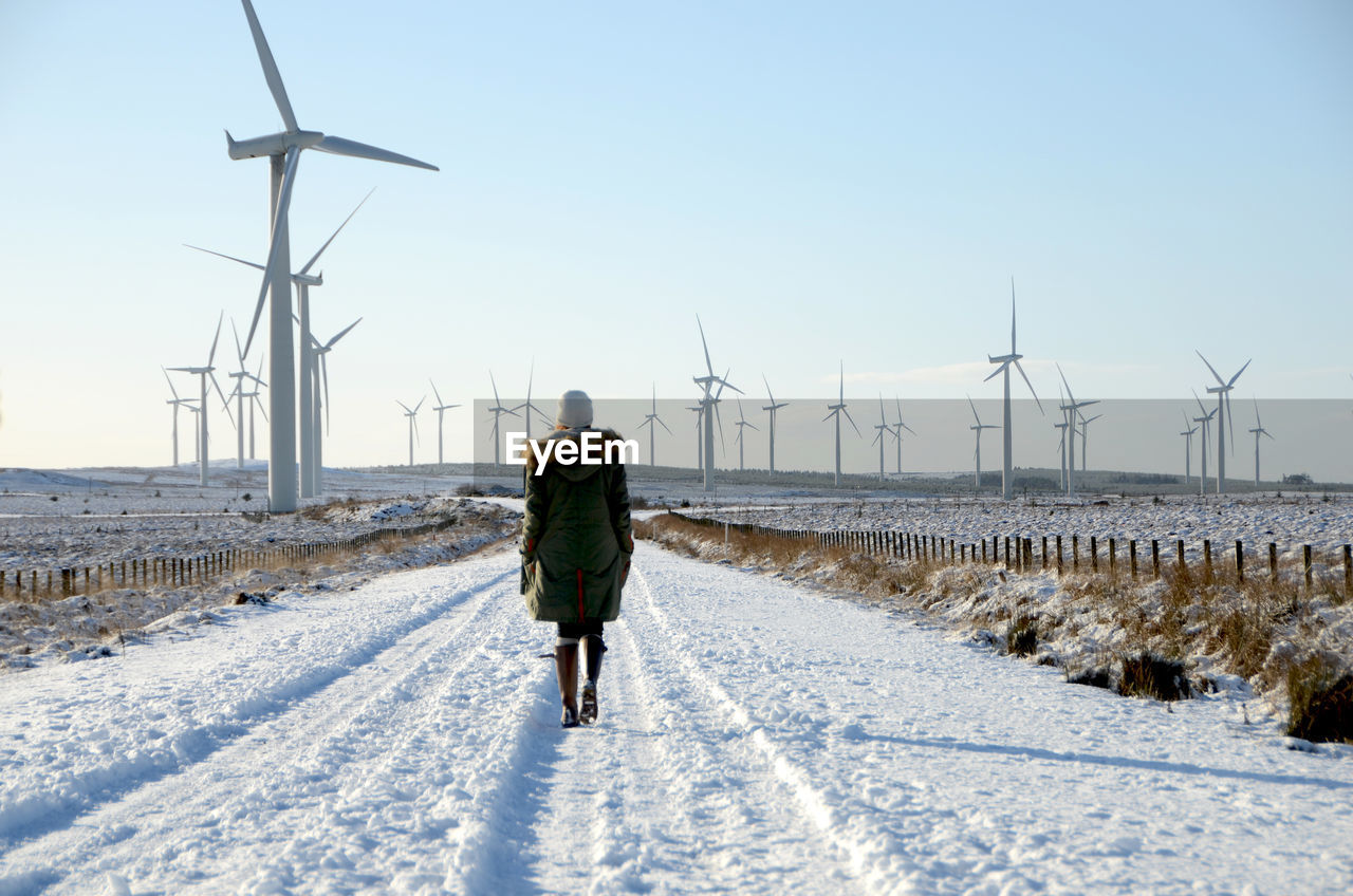 Woman Walking On Snow Covered Road Against Wind Turbines