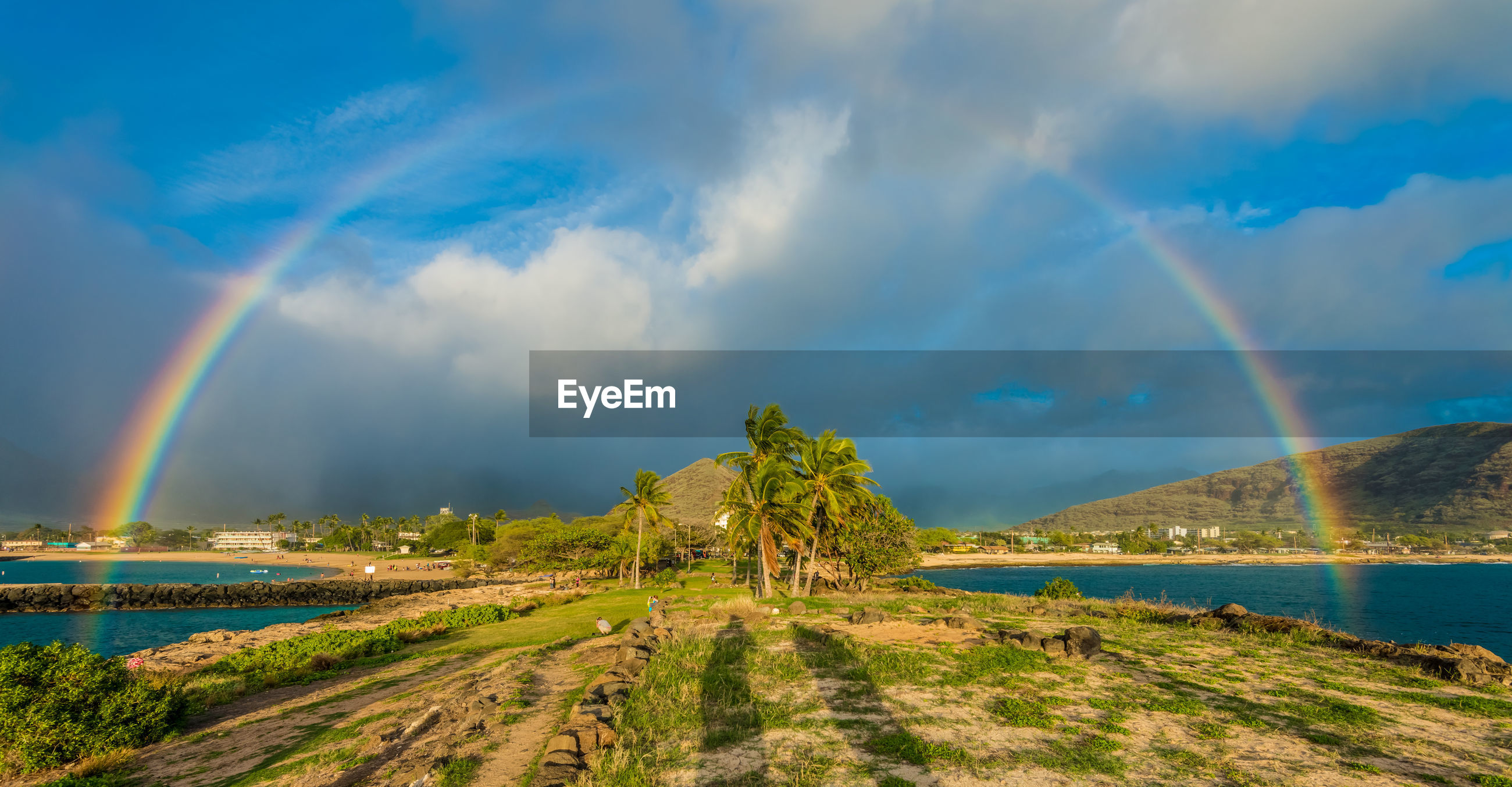 PANORAMIC SHOT OF RAINBOW OVER RIVER AGAINST SKY
