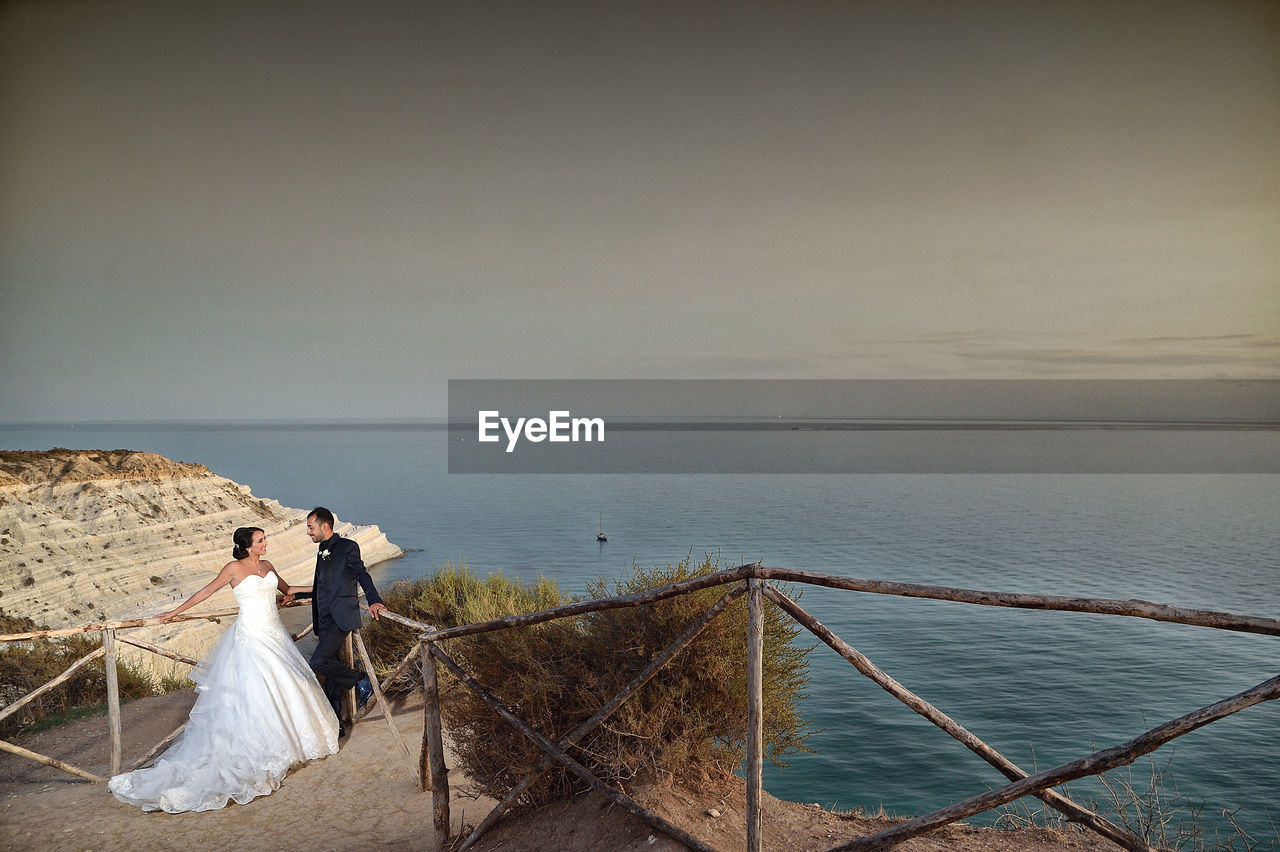sea, water, bride, wedding, wedding dress, horizon over water, nature, railing, scenics, beauty in nature, togetherness, love, outdoors, life events, sky, standing, real people, women, clear sky, bridegroom, beach, men, groom, full length, day, young adult, people