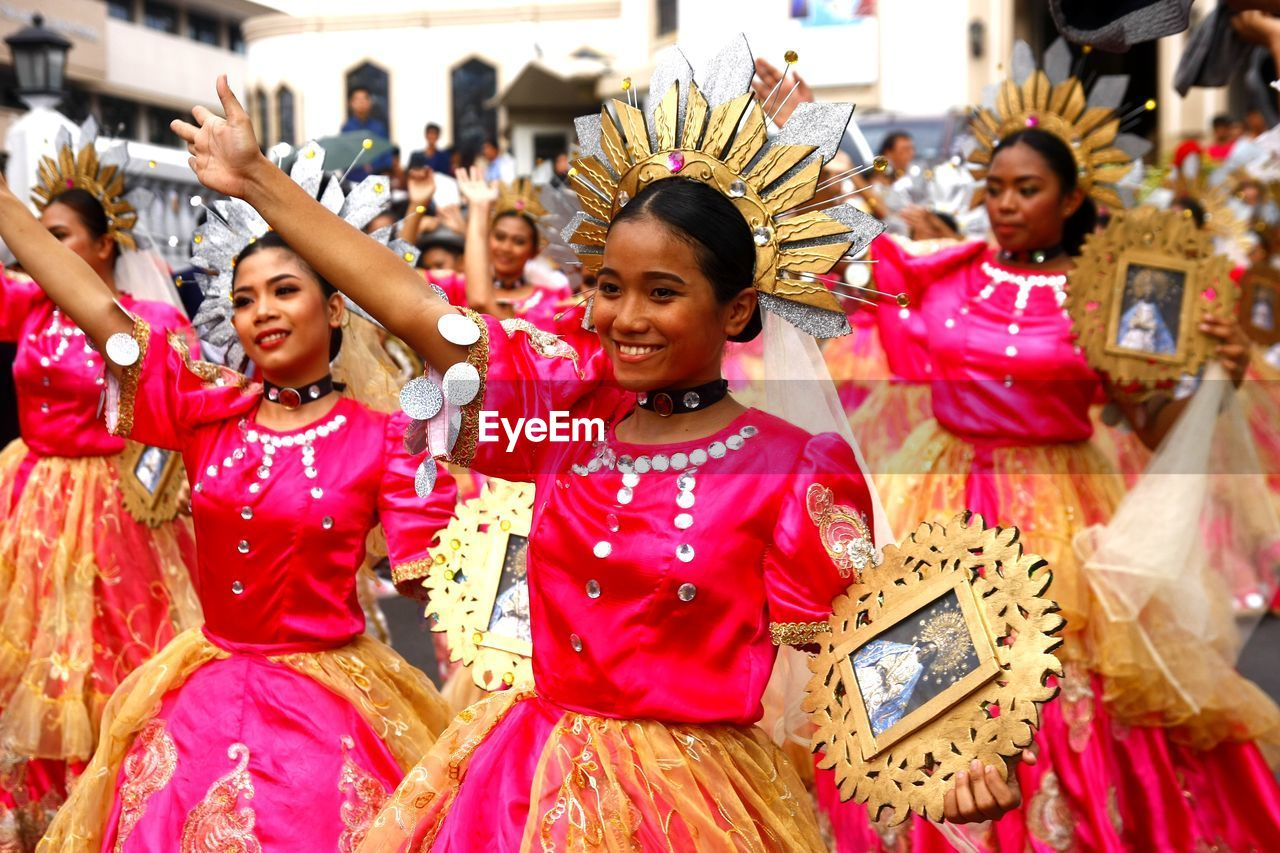 traditional clothing, smiling, happiness, group of people, women, clothing, real people, celebration, adult, emotion, togetherness, lifestyles, large group of people, event, focus on foreground, leisure activity, crowd, positive emotion, festival, traditional dancing