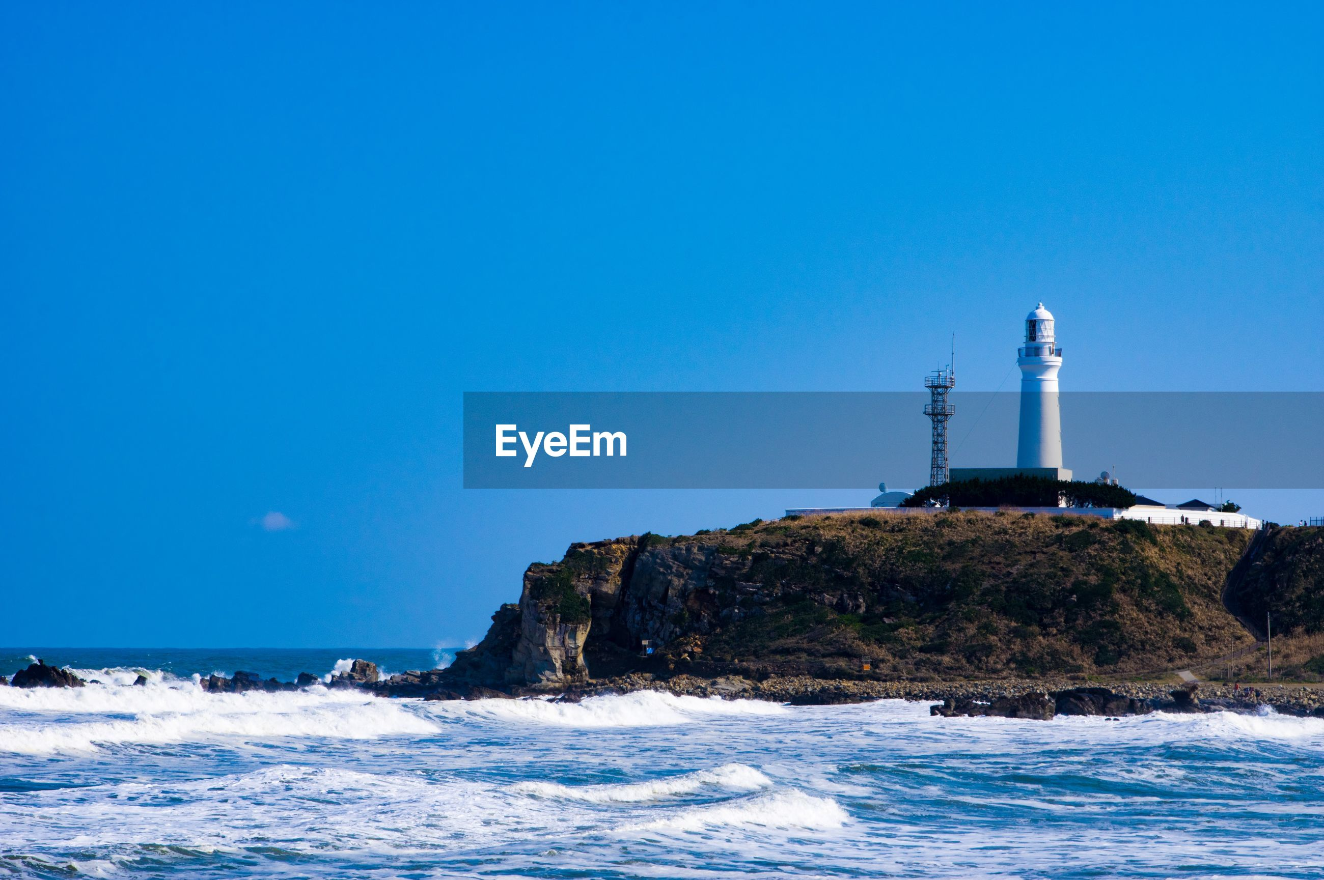 sea, water, lighthouse, sky, tower, clear sky, guidance, built structure, nature, blue, waterfront, land, wave, architecture, no people, copy space, beauty in nature, scenics - nature, building exterior, outdoors, horizon over water, power in nature