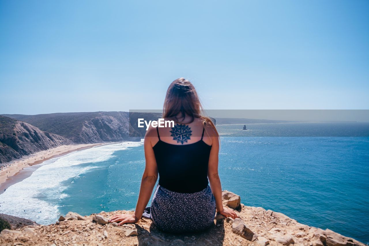 Rear view of young woman sitting on cliff against sea