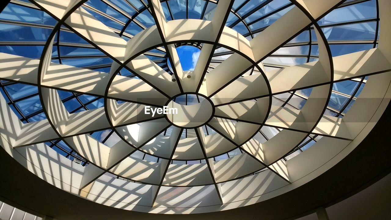 pattern, built structure, geometric shape, ceiling, shape, no people, architecture, indoors, low angle view, design, dome, circle, sunlight, day, glass - material, close-up, decoration, skylight, hanging, cupola, directly below, ornate, luxury
