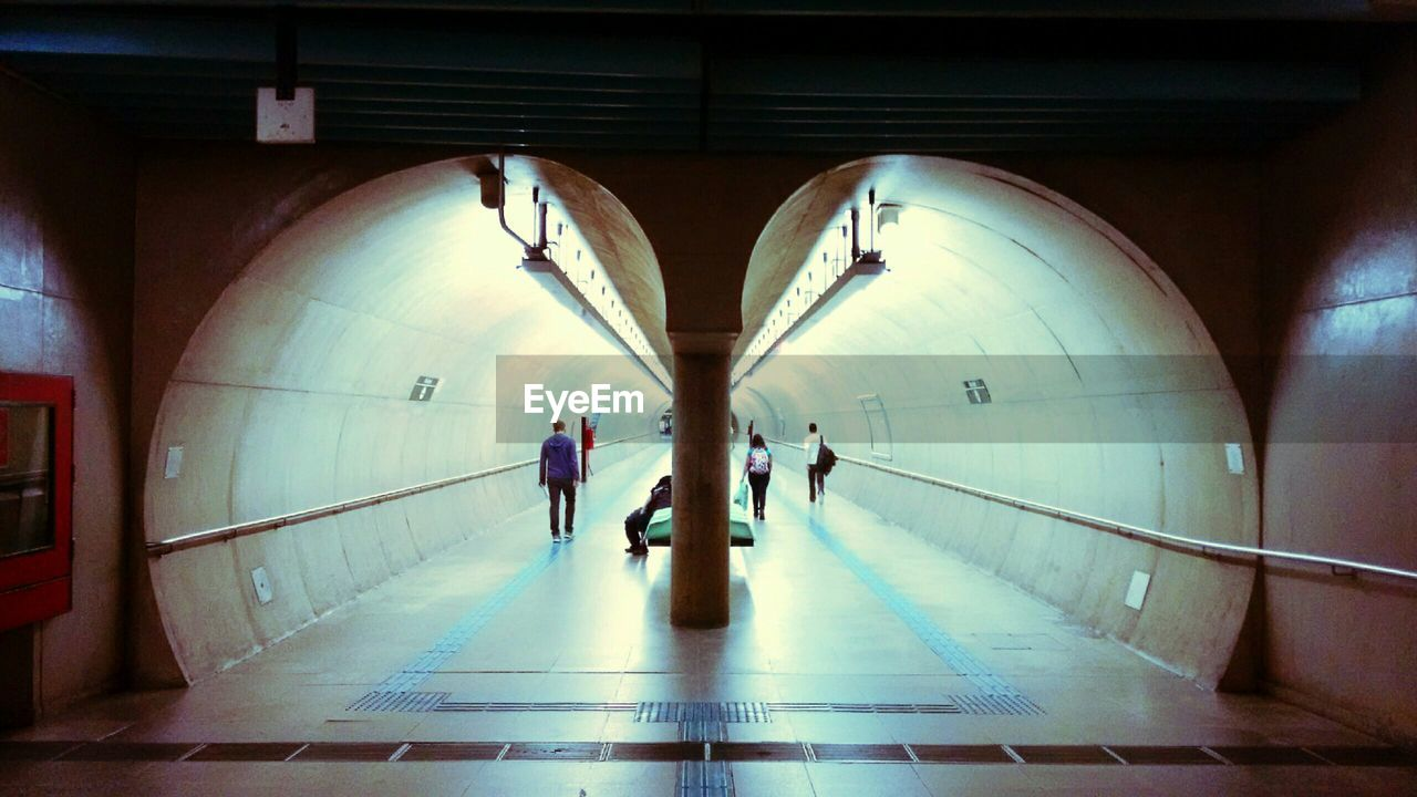 architecture, group of people, indoors, walking, built structure, real people, transportation, direction, arch, the way forward, rear view, public transportation, illuminated, subway, men, subway station, lifestyles, people, flooring, travel, underground walkway, tiled floor