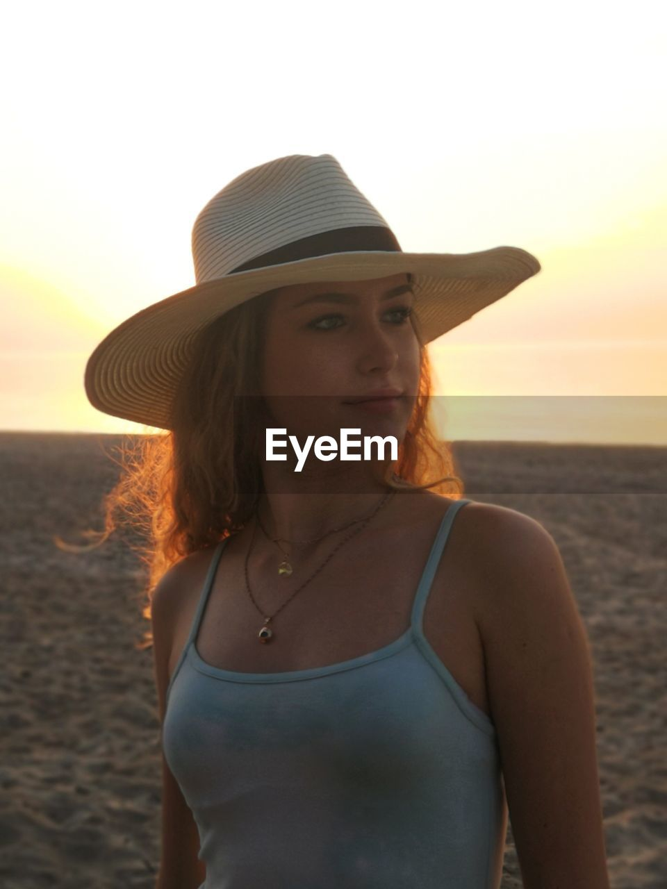 Beautiful woman standing at beach against sky during sunset