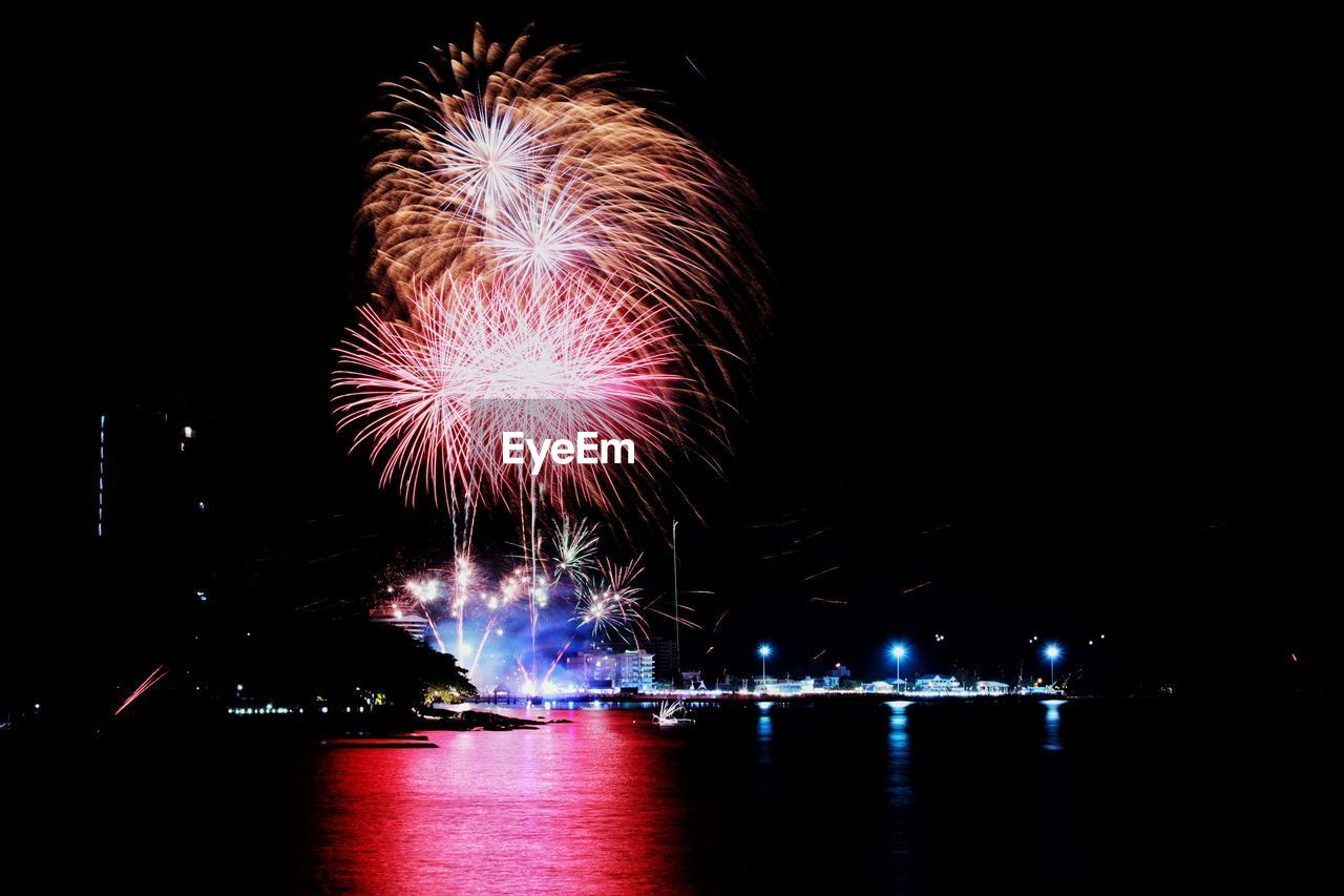night, illuminated, firework, motion, arts culture and entertainment, celebration, firework display, water, exploding, event, long exposure, glowing, sky, architecture, river, firework - man made object, nature, multi colored, reflection, no people, sparks, light, outdoors