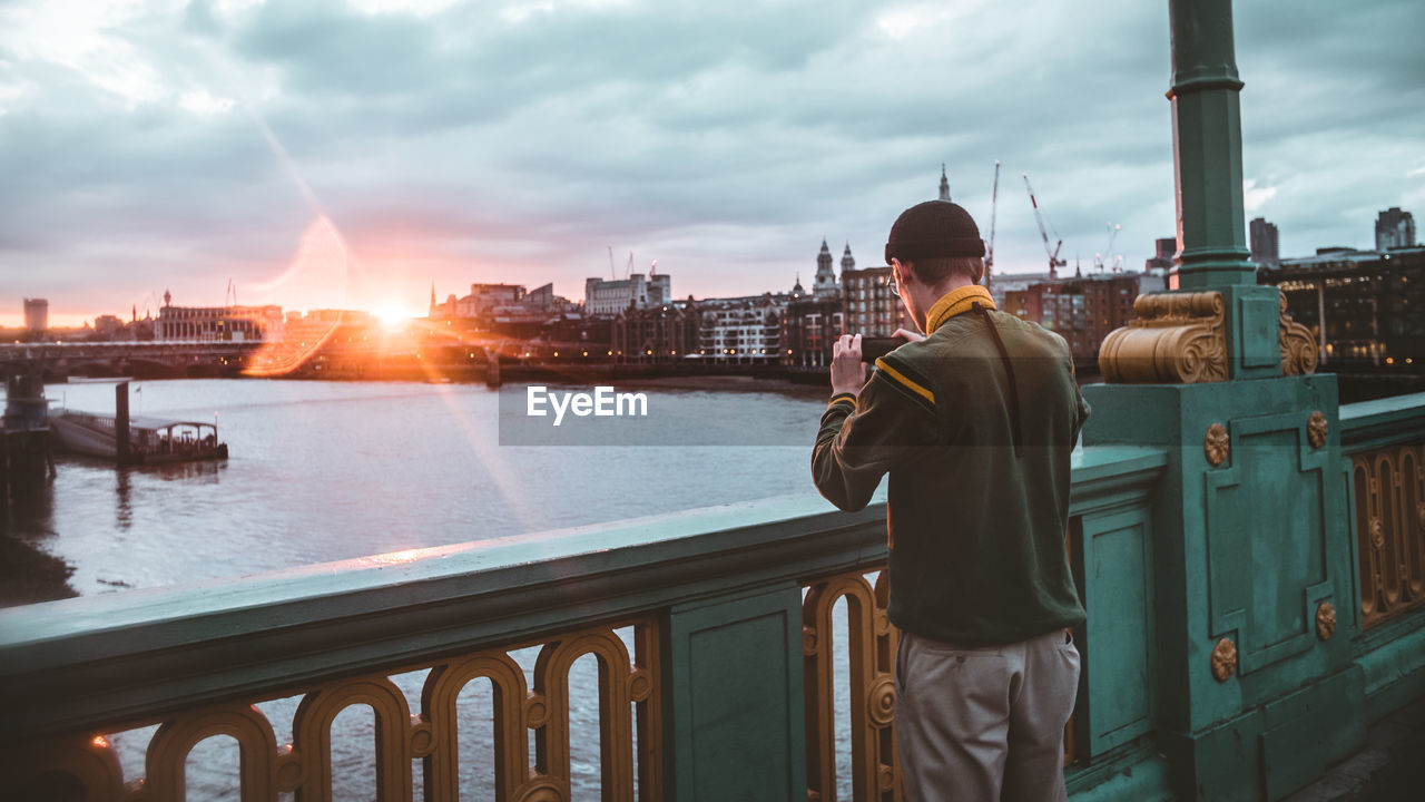 Man Photographing River Through Mobile Phone During Sunset
