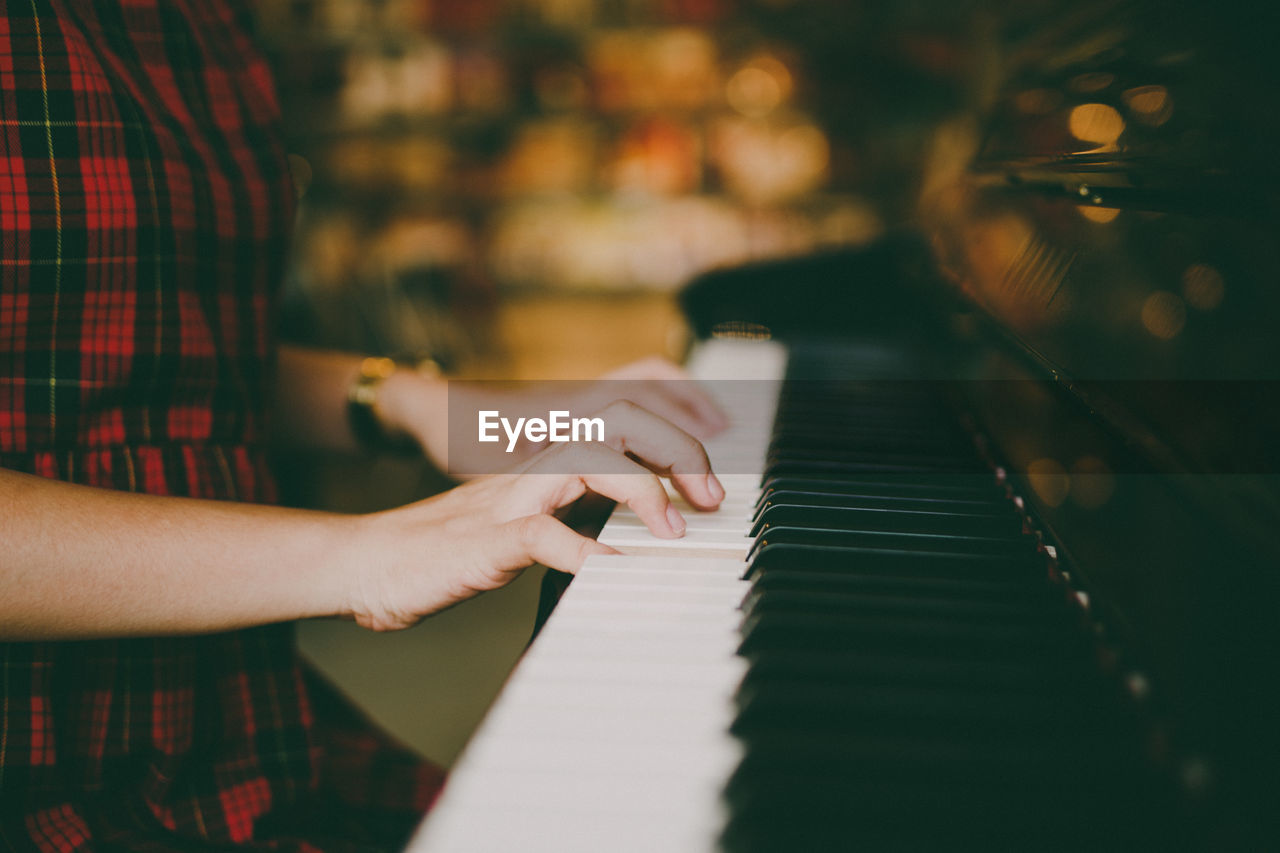 Midsection of young woman playing piano