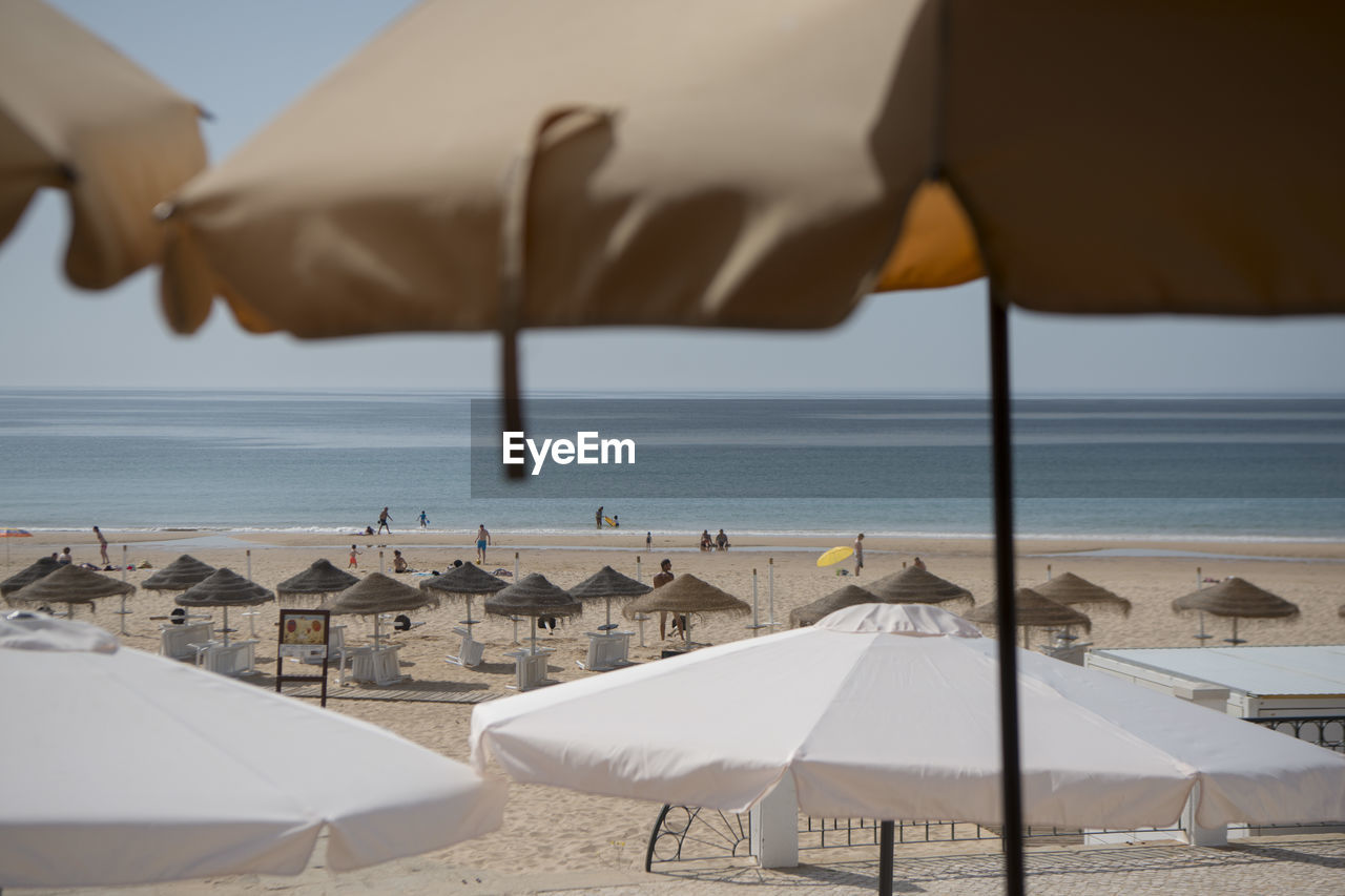 Open Parasols At Beach On Sunny Day