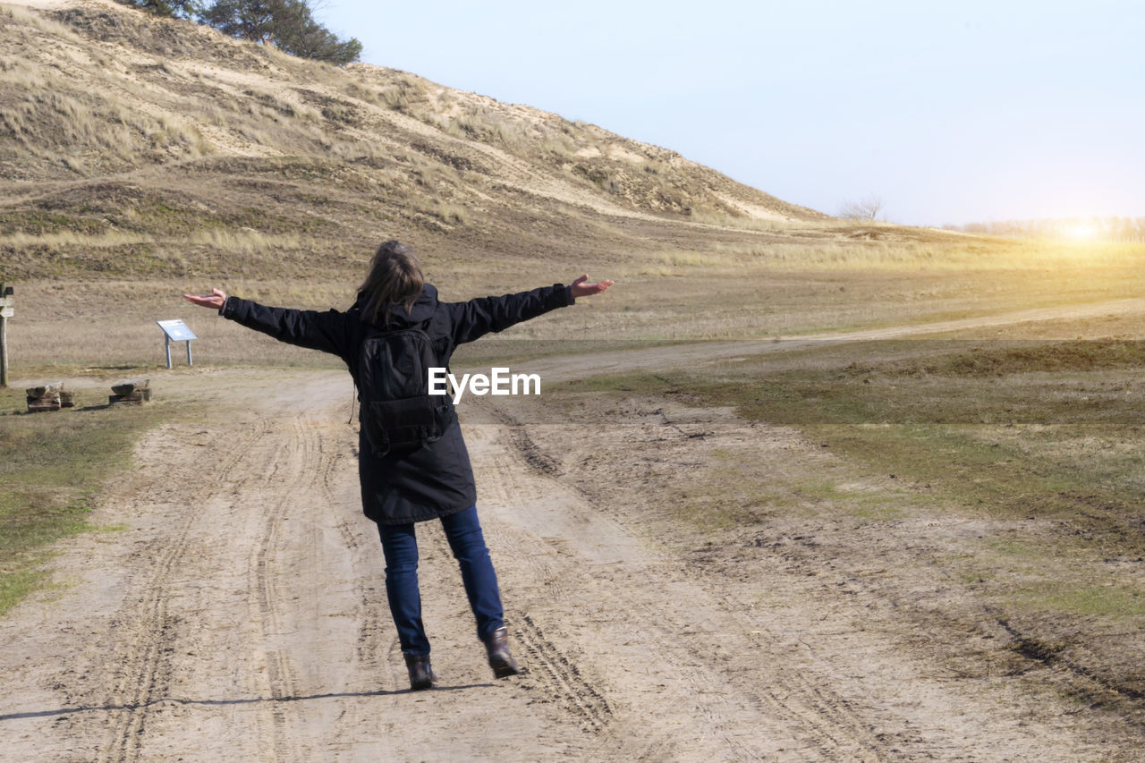 one person, leisure activity, landscape, full length, environment, arms outstretched, lifestyles, human arm, real people, day, limb, rear view, nature, standing, sky, adult, casual clothing, scenics - nature, road, outdoors, arms raised, freedom, human limb