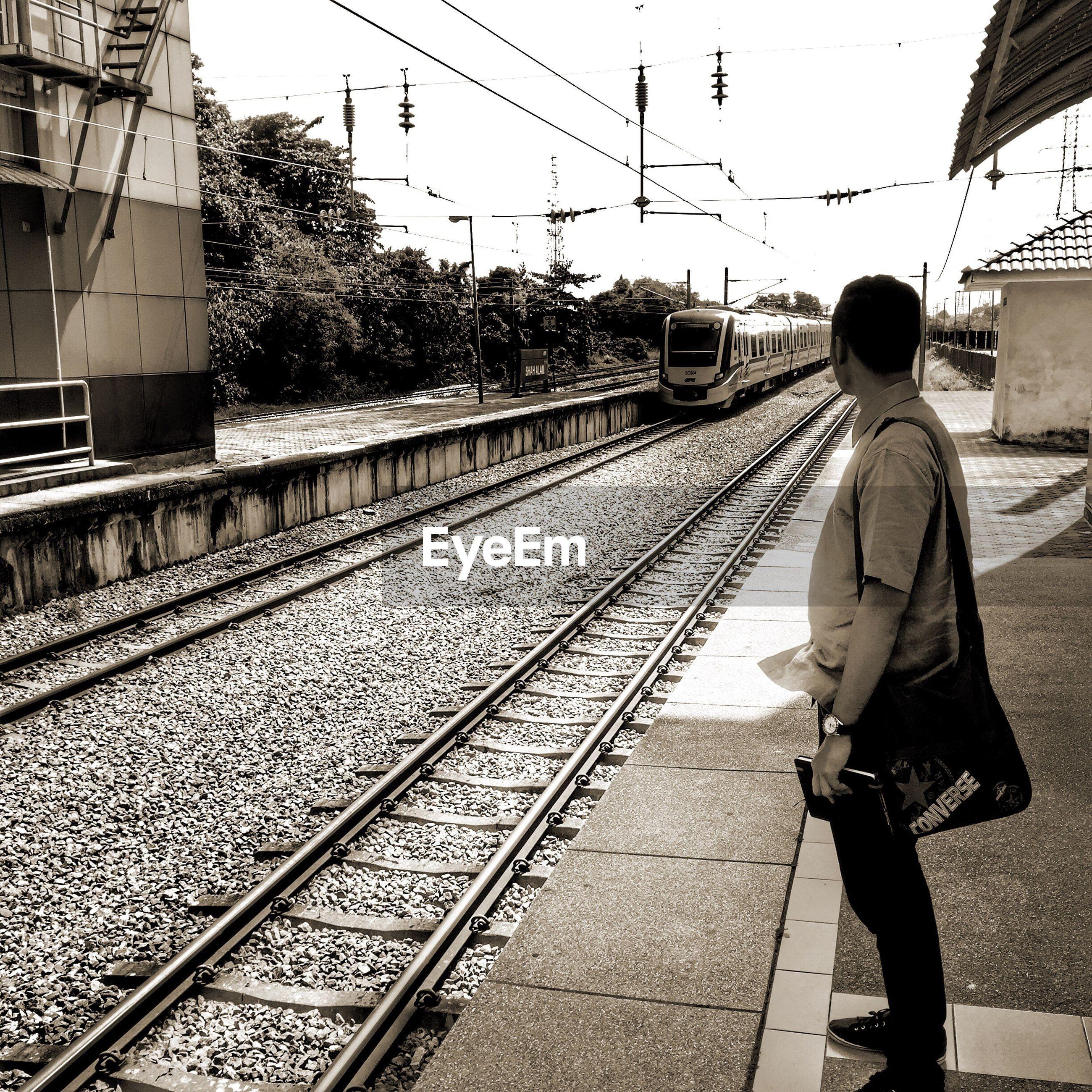 railroad track, transportation, rail transportation, railroad station platform, lifestyles, rear view, men, public transportation, full length, railroad station, walking, the way forward, leisure activity, built structure, travel, connection, architecture, diminishing perspective