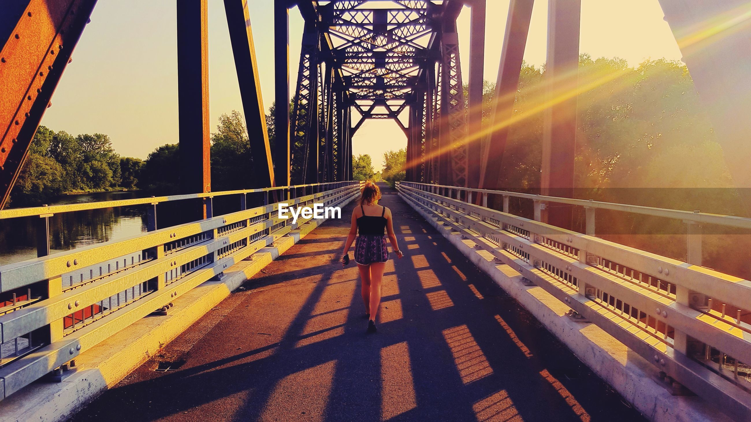 Rear view of young woman walking on bridge during sunset