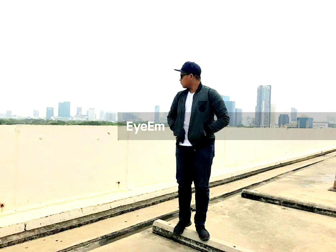 full length, one person, city, real people, standing, built structure, architecture, men, cityscape, building exterior, lifestyles, young men, outdoors, clear sky, skyscraper, technology, day, young adult, sky, businessman, urban skyline, adult, people