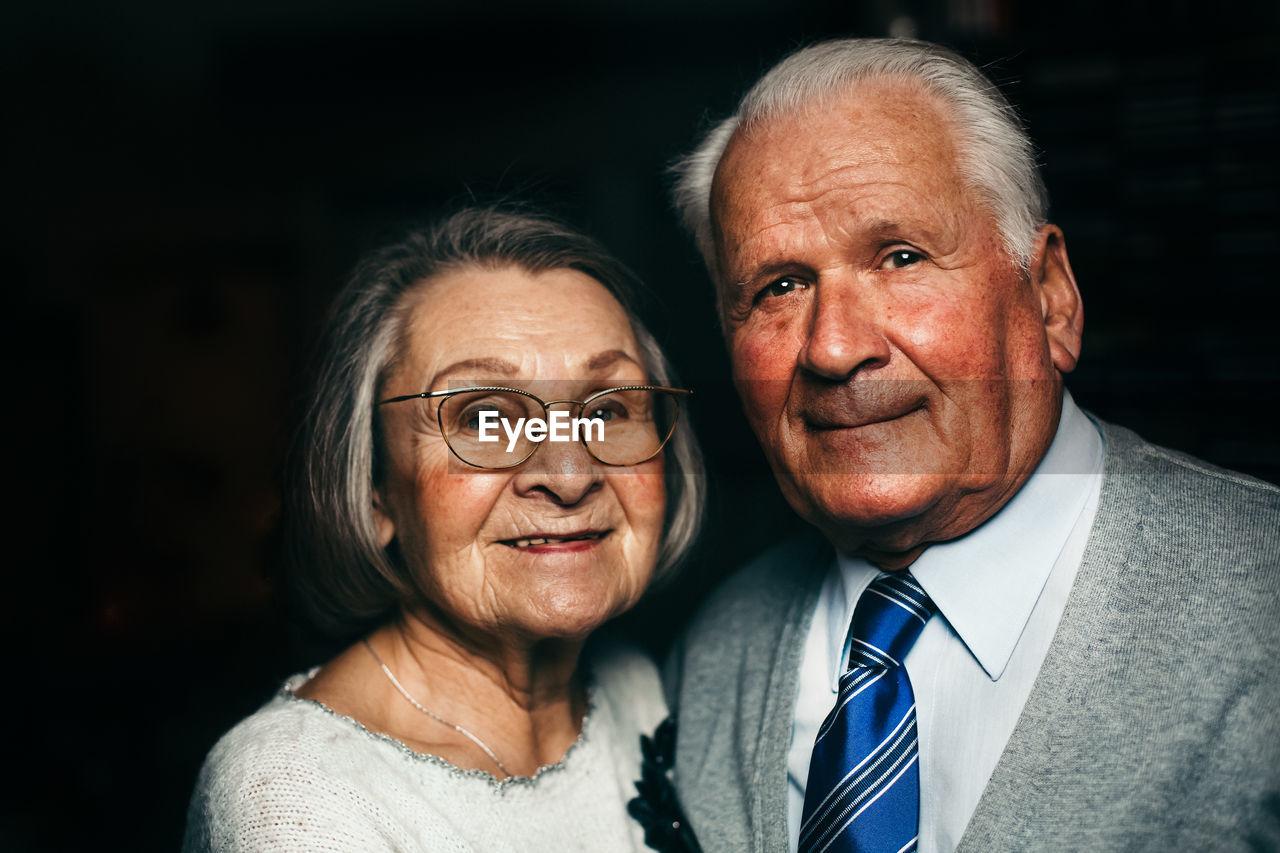 Close-up portrait of senior couple smiling in darkroom