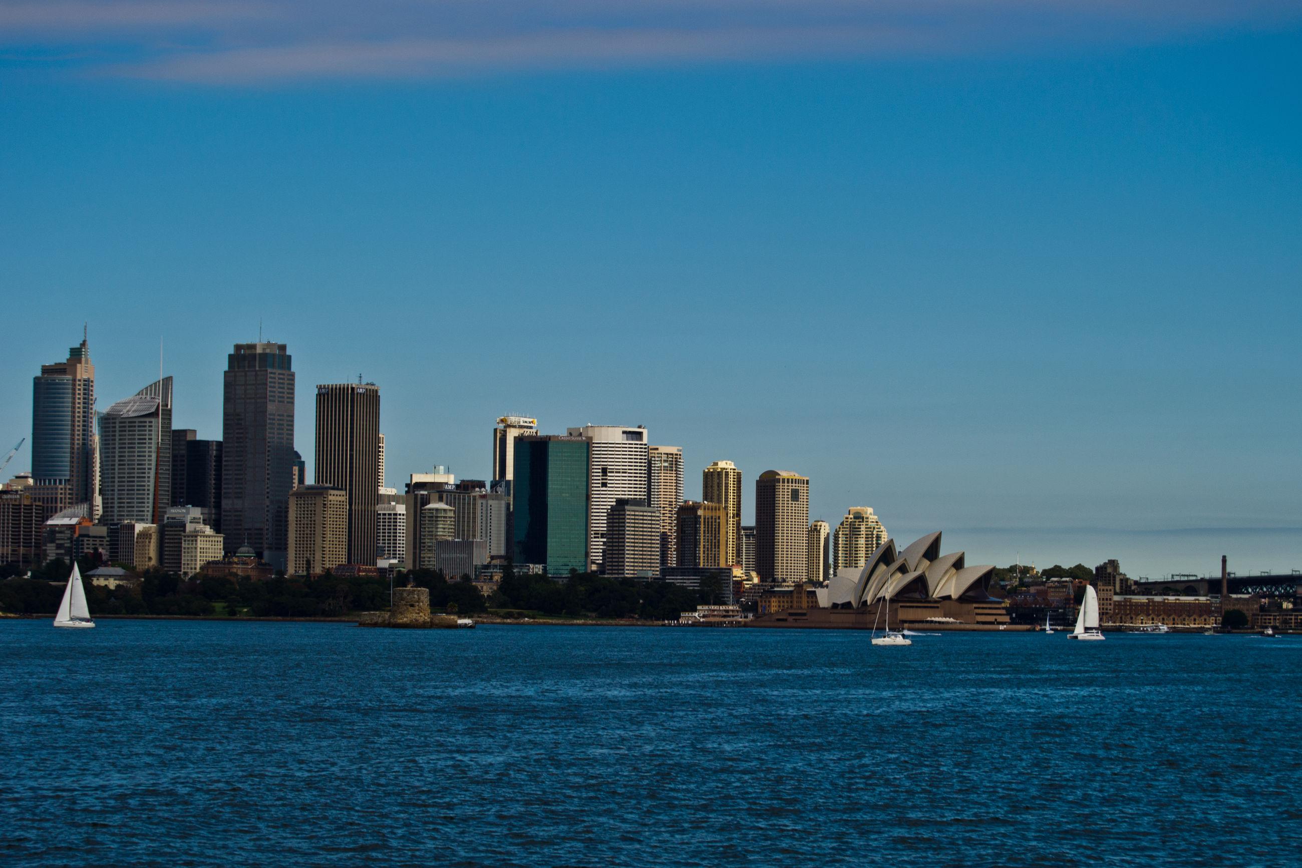 SEA BY CITY BUILDINGS AGAINST CLEAR BLUE SKY
