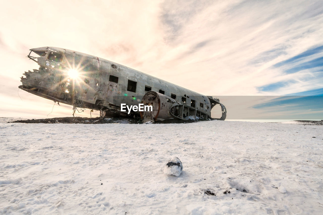 Abandoned airplane crash on snowy field against sky during sunset