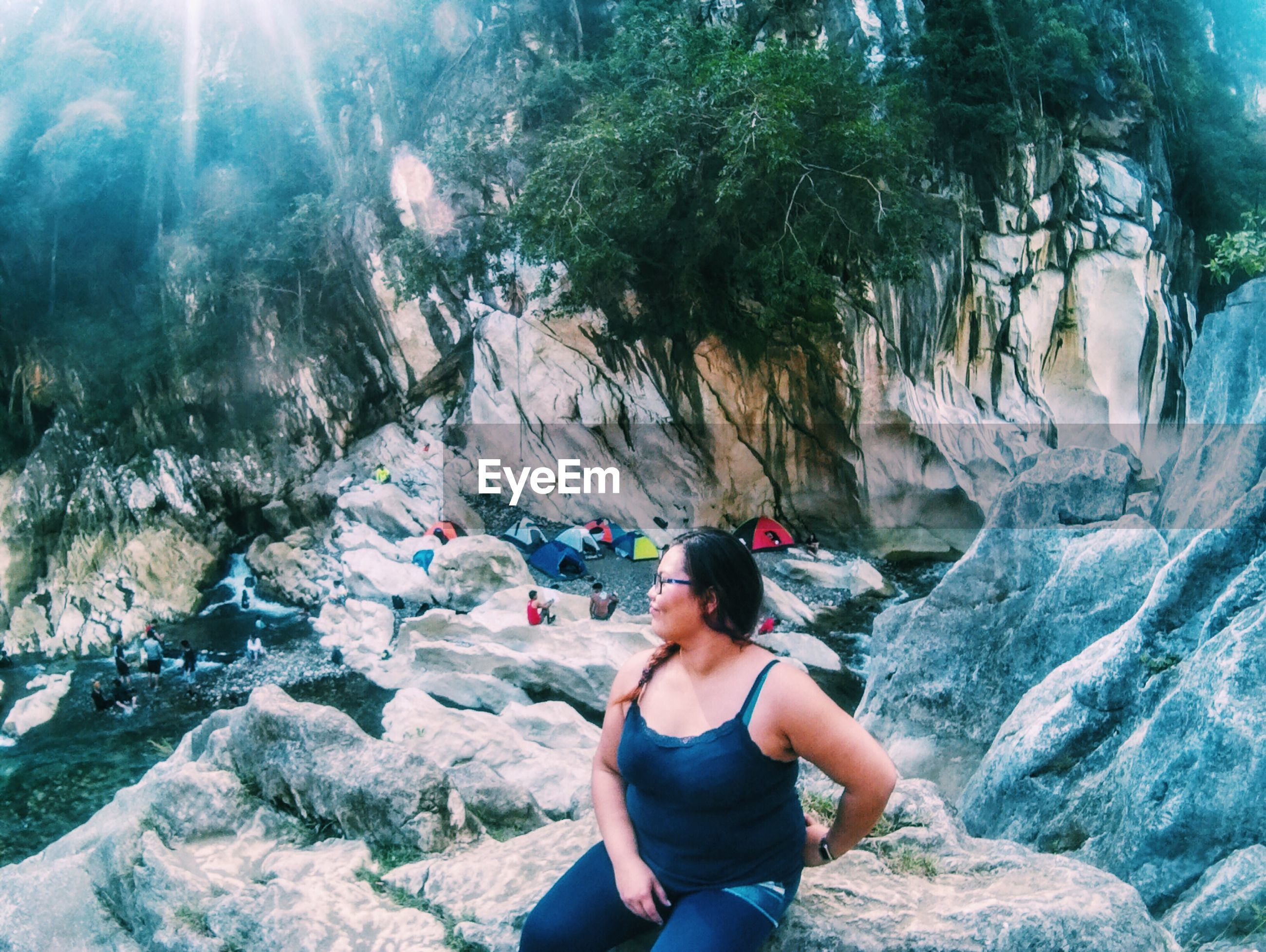 Woman sitting on rocks by river